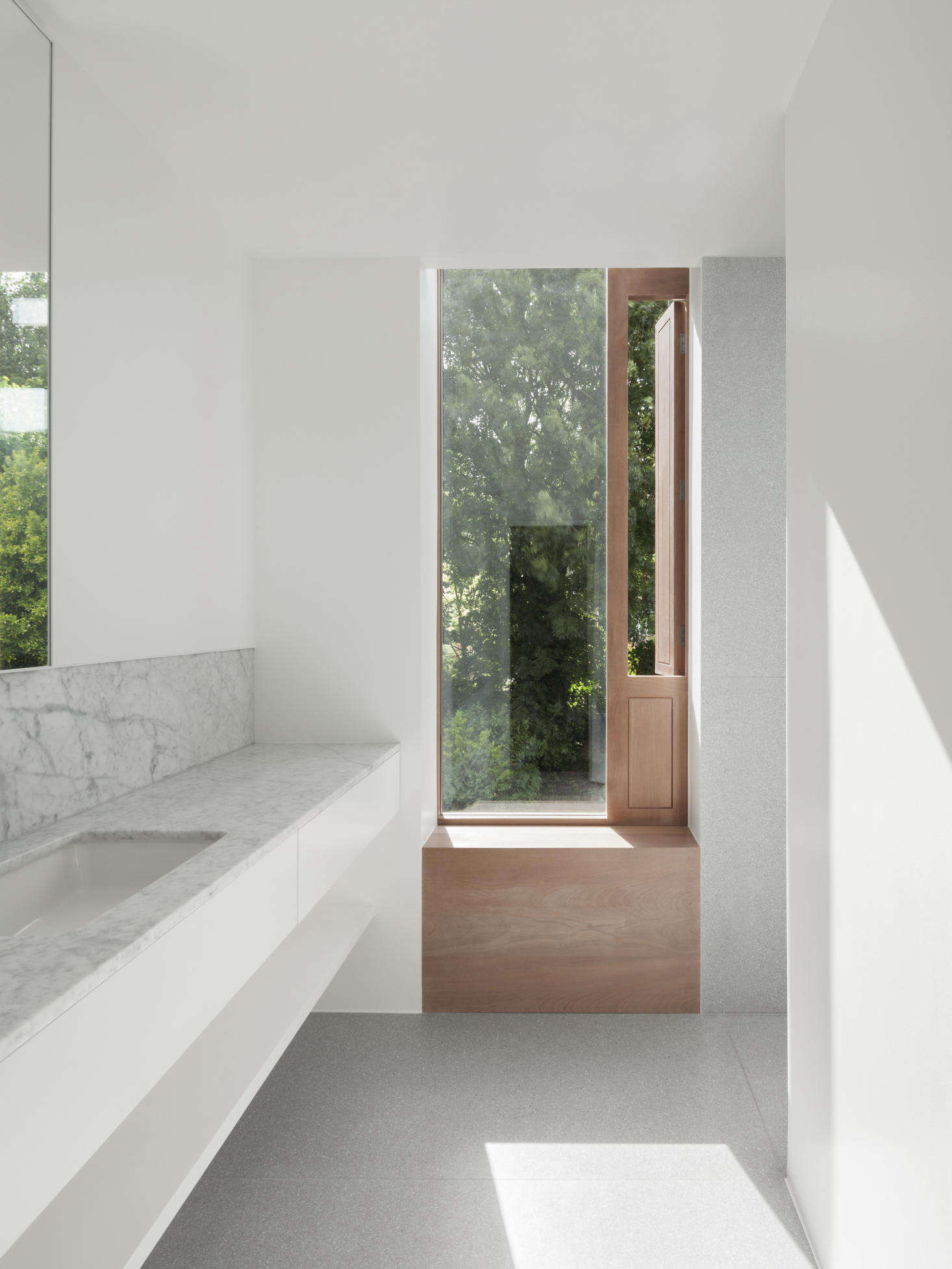 The first-floor bathroom was refurbished as part of the project. The architects installed a glass panel window with a sapele wood frame and single shutter for ventilation. Countertops, as in the kitchen, are Carrara marble from Rossi Stoneworks and the floors are Terrazzo Cement by In Opera Group.