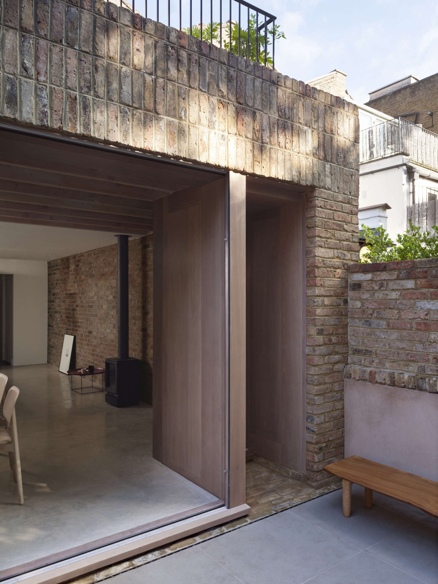 A detail of the extension, which opens onto a sunken brick and concrete paver patio. The live-edge bench is made from a single oak plank from Andrea and Pete's previous garden in Suffolk that was customized with oak legs byAndrew Tutka.
