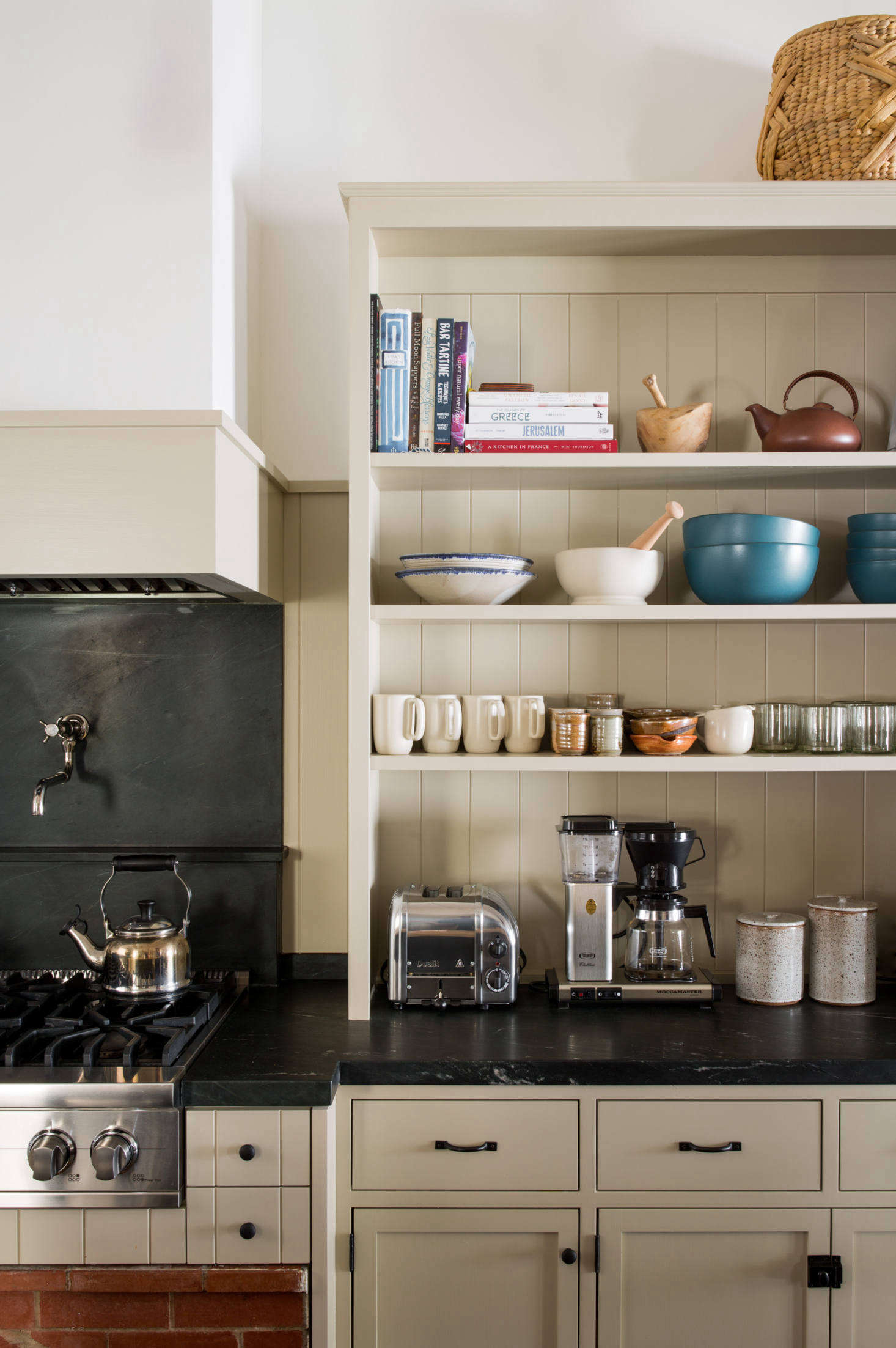 The custom cabinets have V-groove fronts that match the wainscoting and the original cladding elsewhere in the house. (For more, consult The Ultimate Wood Paneling Guide.) Above the stove is a pot filler by Waterworks and a Le Creusetkettle. The toaster is Dualit&#8
