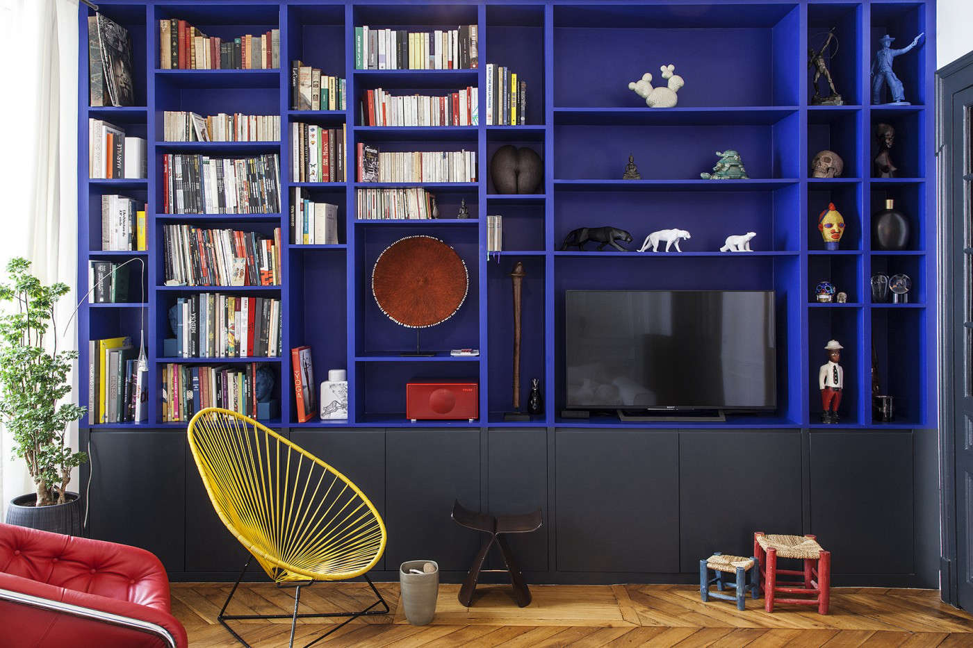 The bookshelf in question: striking built-ins painted in a bold Yves Klein lookalike in a Paris apartment by Batiik Studio.
