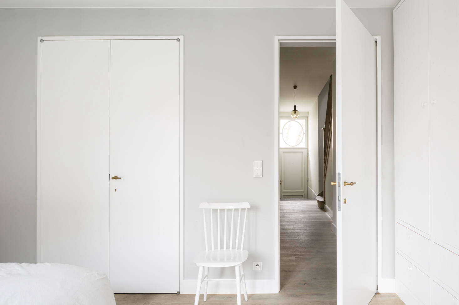 On the ground floor, one flight down, is the master bedroom, set back from the street for maximum privacy. It's painted in a pale gray, with subtle brass hardware from family-owned Belgian company Jaro Style, which the architects used throughout, and a white ladder-back chair from Dille & Kamille.