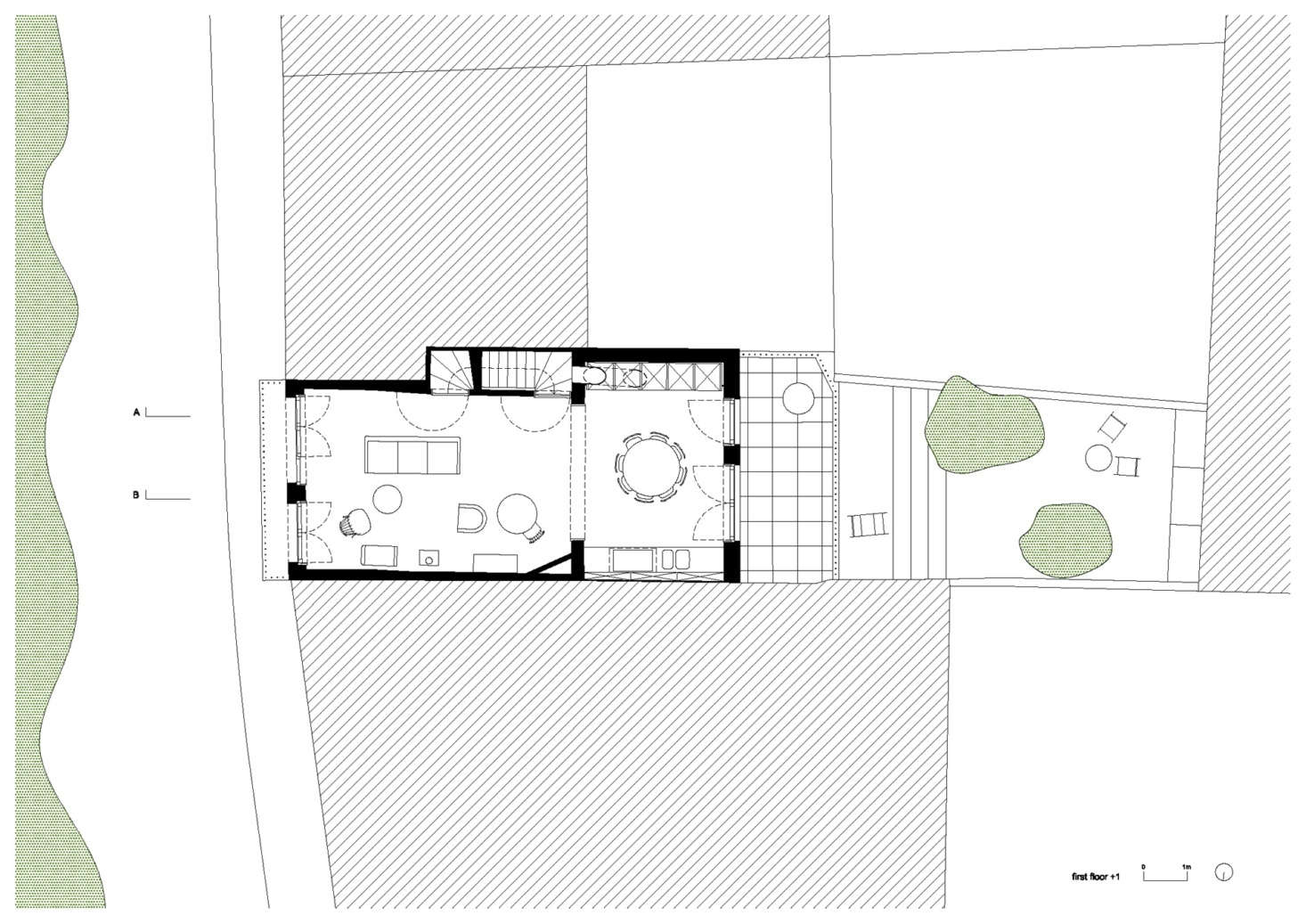 "The next floor up, showing the living area and kitchen, with the staircase and cabinetry set into the walls. This floor also opens onto the balcony (on the street side) and a sunny terrace (in back). There is a top floor, which the architects say is fitted with ""guest amenities."""