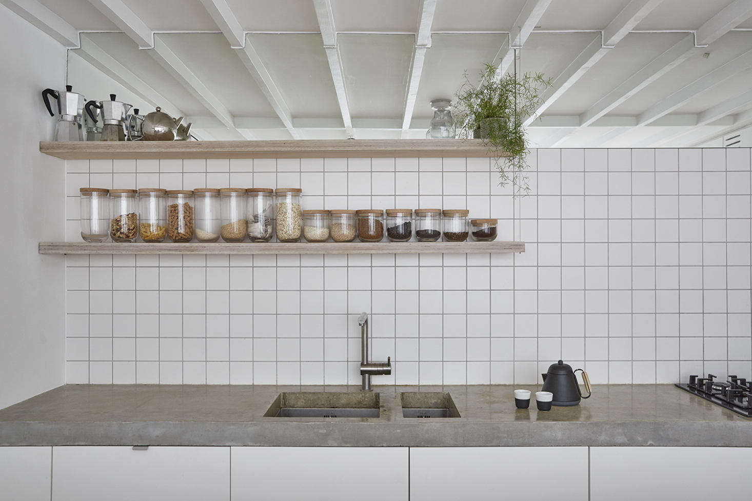A clevertrompe l'oleil: Hutchinson fitted an expanse of mirror at the top of the tiled backsplash: It reflects the ceiling and makes the room seem bigger. The faucet is byGrohe; the undermount sinks are byGEC Anderson.