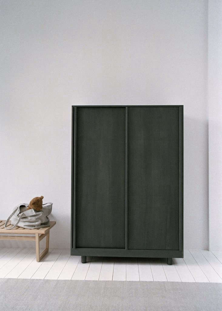 The ashWardrobe with Sliding Doors is stained forest green; €src=