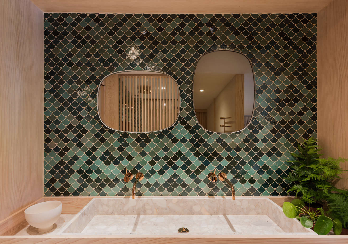 Two Vola polished brass faucets jut from a wall of handmade Moroccan tiles, in varying shades of green, from Emery et Cie. Photograph by Michelle Young, courtesy of StudioUlanowski, from House Tour: A Flexible Pied-à-Terre in London for a Jewelry Designer and Her Family.