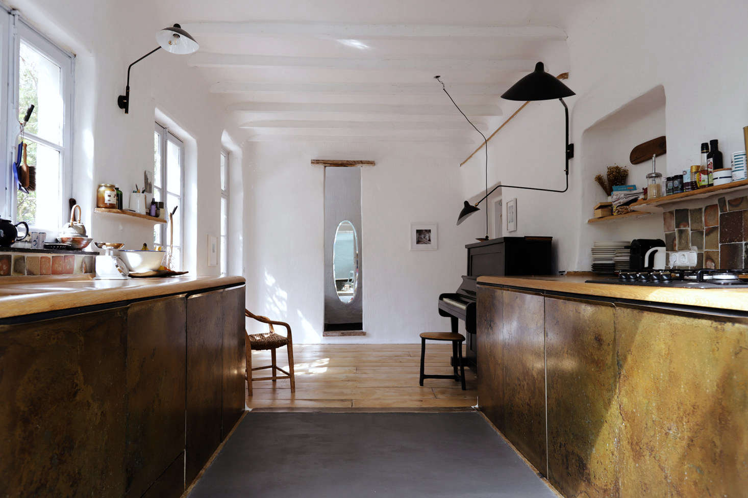 The kitchen floor is Wall2Floormicro-cement with radiant heating beneath. The lights are Serge Mouille: the 1-Arm Rotating Sconce and 2-Arm Rotating Sconce.