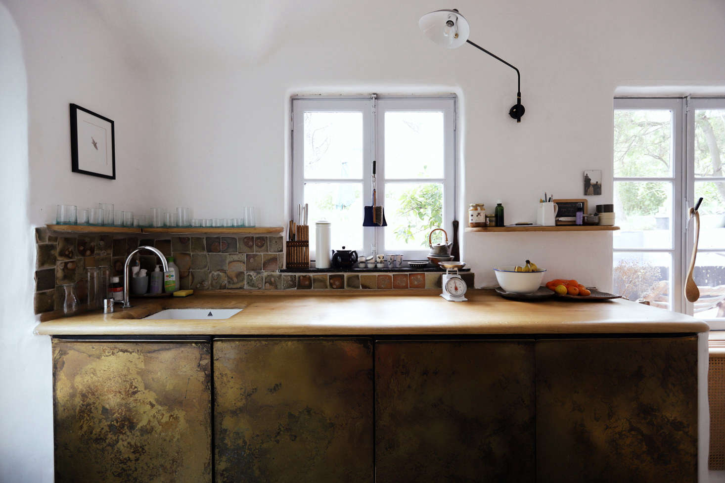 """The kitchen is entirely new, though Valentin says, """"there really wasn't anything there before to remove."""" The cabinets are handmade from patinated brass and the counter is carved oak finished with hardwax. The tile backsplash is made from tiles Valentin made in his father's studio (his father is a ceramicist) as a child. The porcelain kitchen sink was found in the basement of the house."""