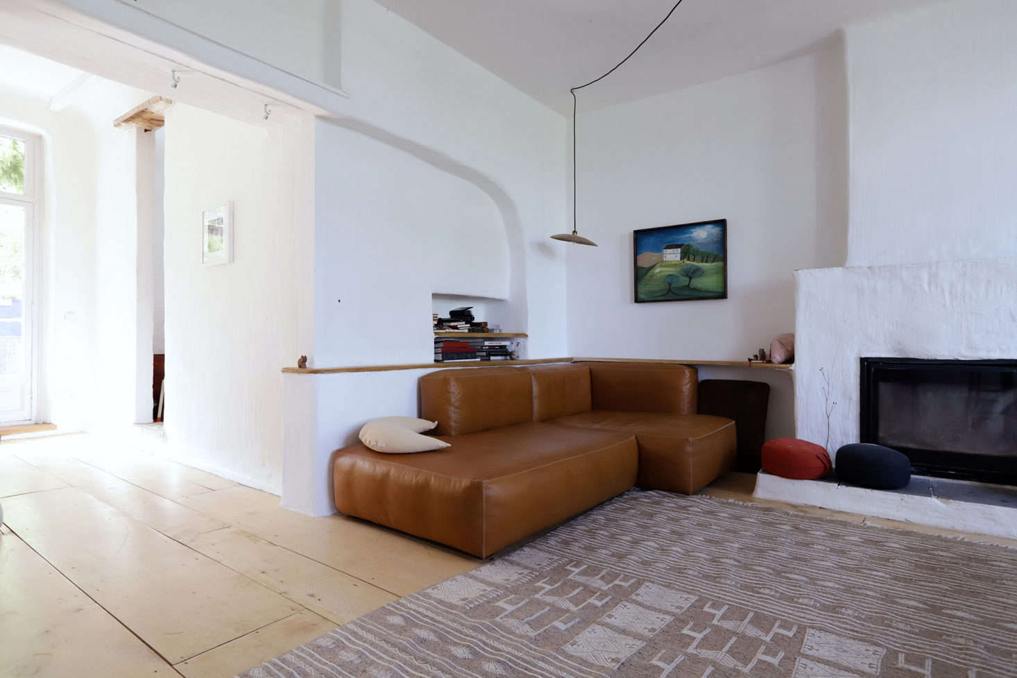 The sofa is a Hay Mags 3-Seater Sofa in leather and the rug is a gift from Valentin's mother, who works in Africa. The floors are made of hand-polished poplar.