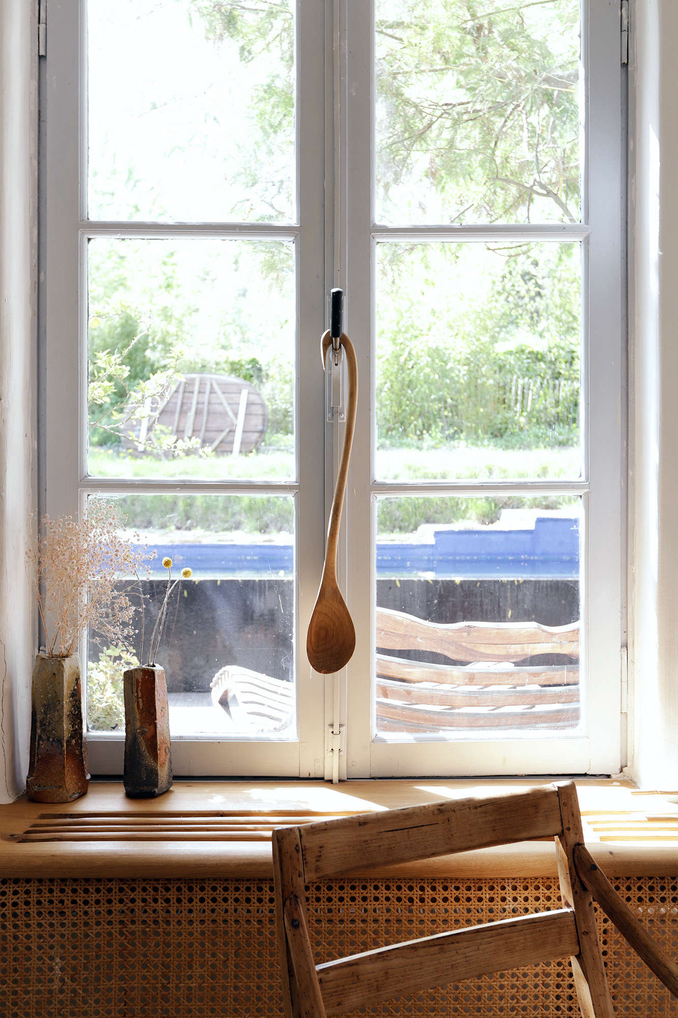 The curved handle of a handmade wooden spoon makes it ideal for dangling from the window latch in designer Valentin Loellmann's Maastricht home. Photograph by Jonas Loellman from 100 Percent Handmade: Valentin Loellmann's Historic River House in Maastricht.