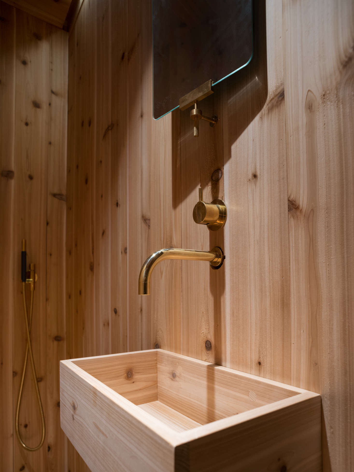 The brass fixtures are by Vola and the brass-framed mirror is the KBH Mirror.