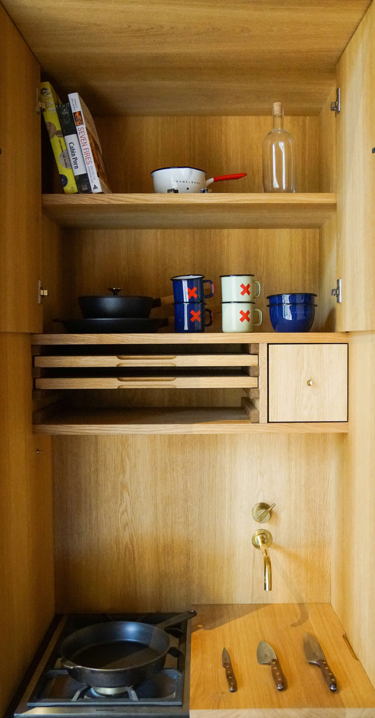 KBH detailed the all-oak design with an overhead cabinet and pullout wooden cutting boards (when one is placed atop the sink, as shown here, it becomes a work counter).