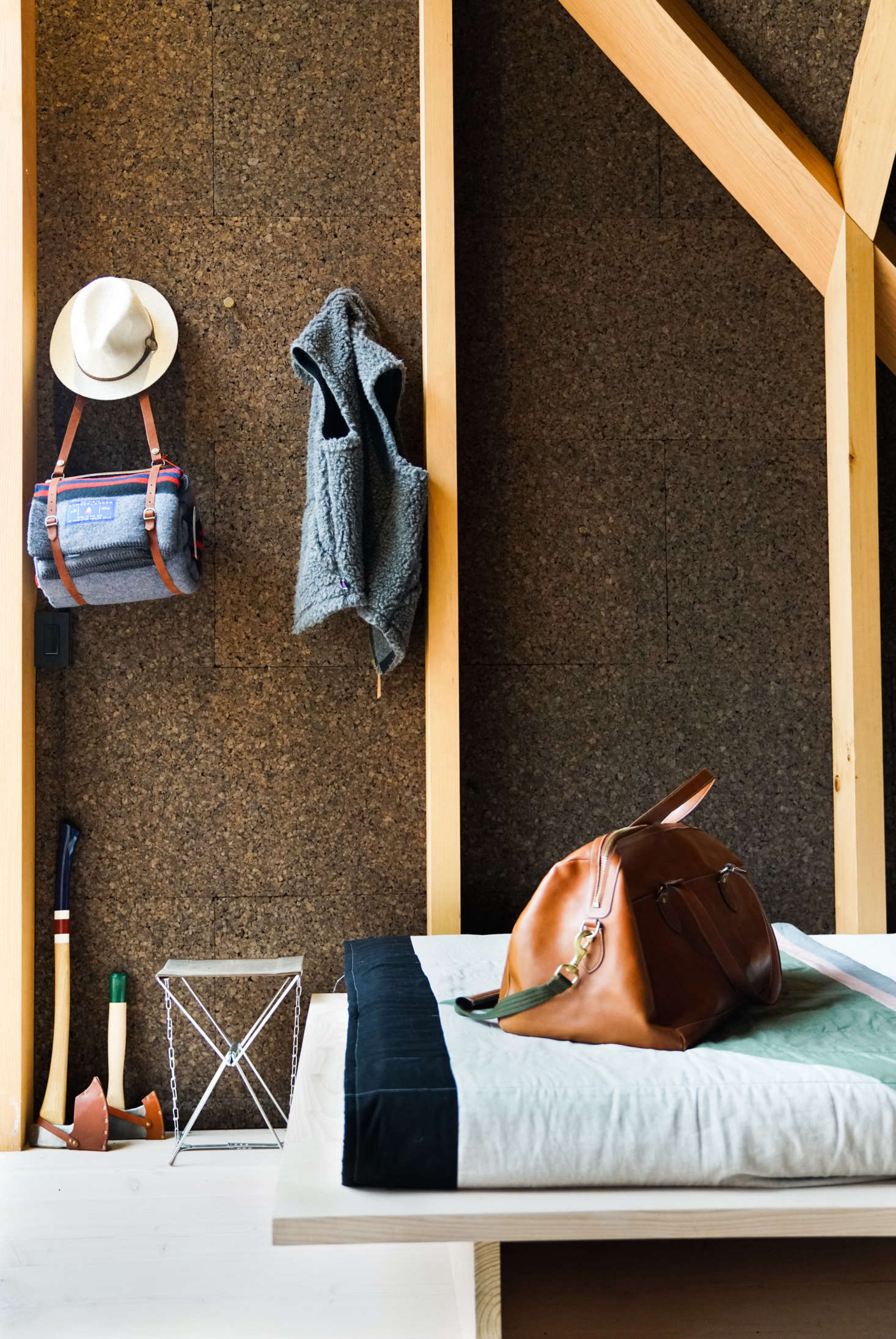 The walls are lined in dark brown cork, which, in addition to being a natural insulator and sound absorber, adds an organic, textured look. The quilt is a Søren Rose Studio design made from Kvadrat fabric. Admiring the camp gear? The hanging Lumberlander Blanket,painted Axes, andThe Waxed Canvas Camp Stool are from Best Made Co.