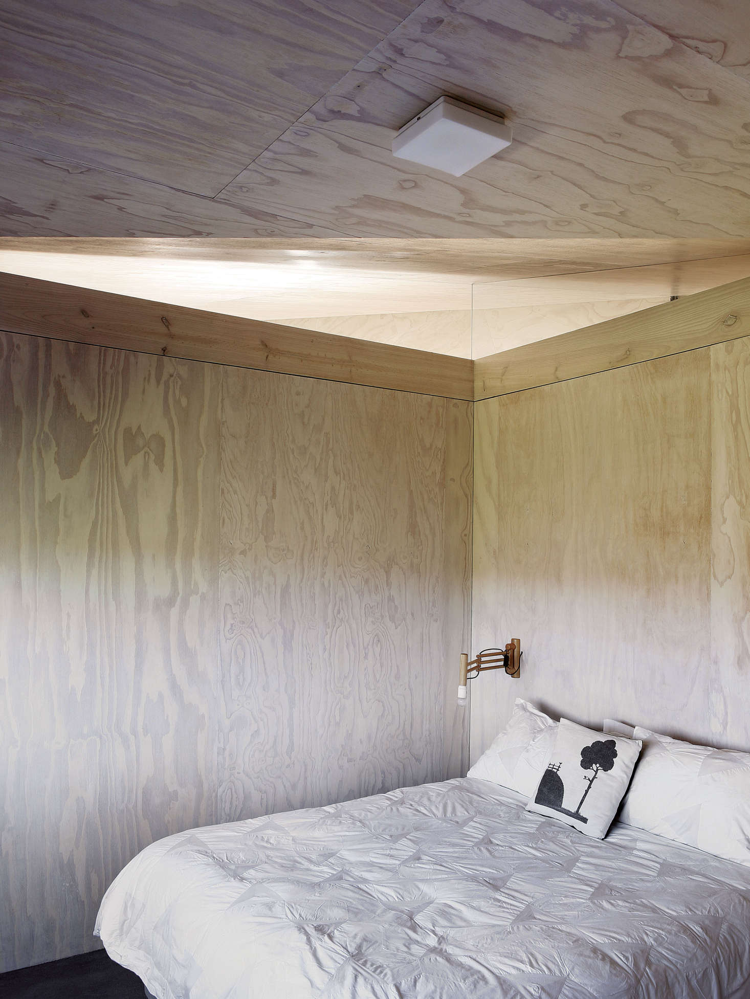 A guest bedroom is kept spare with a ceiling-mount light and vintage wood sconce.