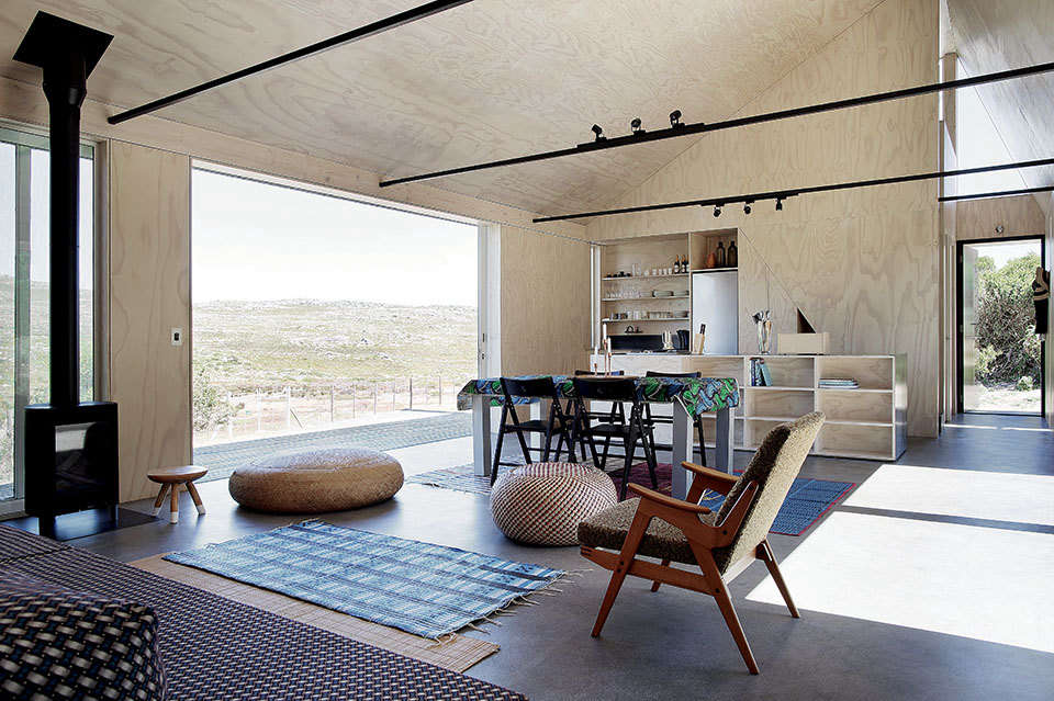 The floors throughout the house are Corcoleum Malpette flooring, a hardwearing composite material made from recycled wood chips. The living and dining spaces are layered with African rugs. The fireplace is a Danish Jøtul GF 0 Gas Stove.