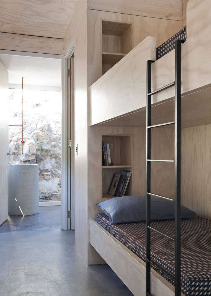 The plywood bunks have storage alcoves and a steel ladder.