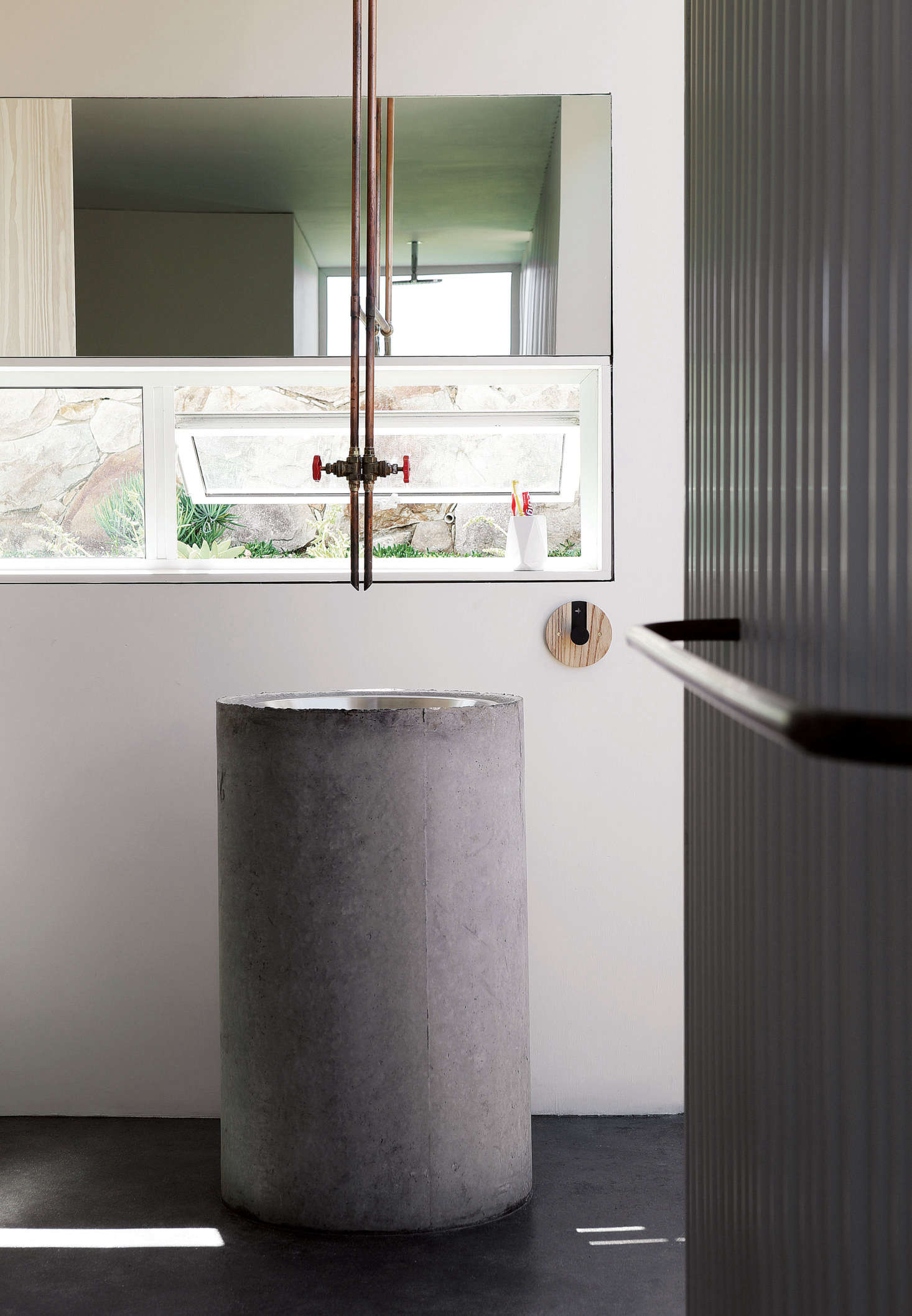 "The architects designed the communal ""bathhouse"" with a large sink made of a stainless steel kitchen prep bowl set into a pre-cast concrete plumbing pipe. The faucet, like the one in the kitchen, is made from copper plumbing pipe."