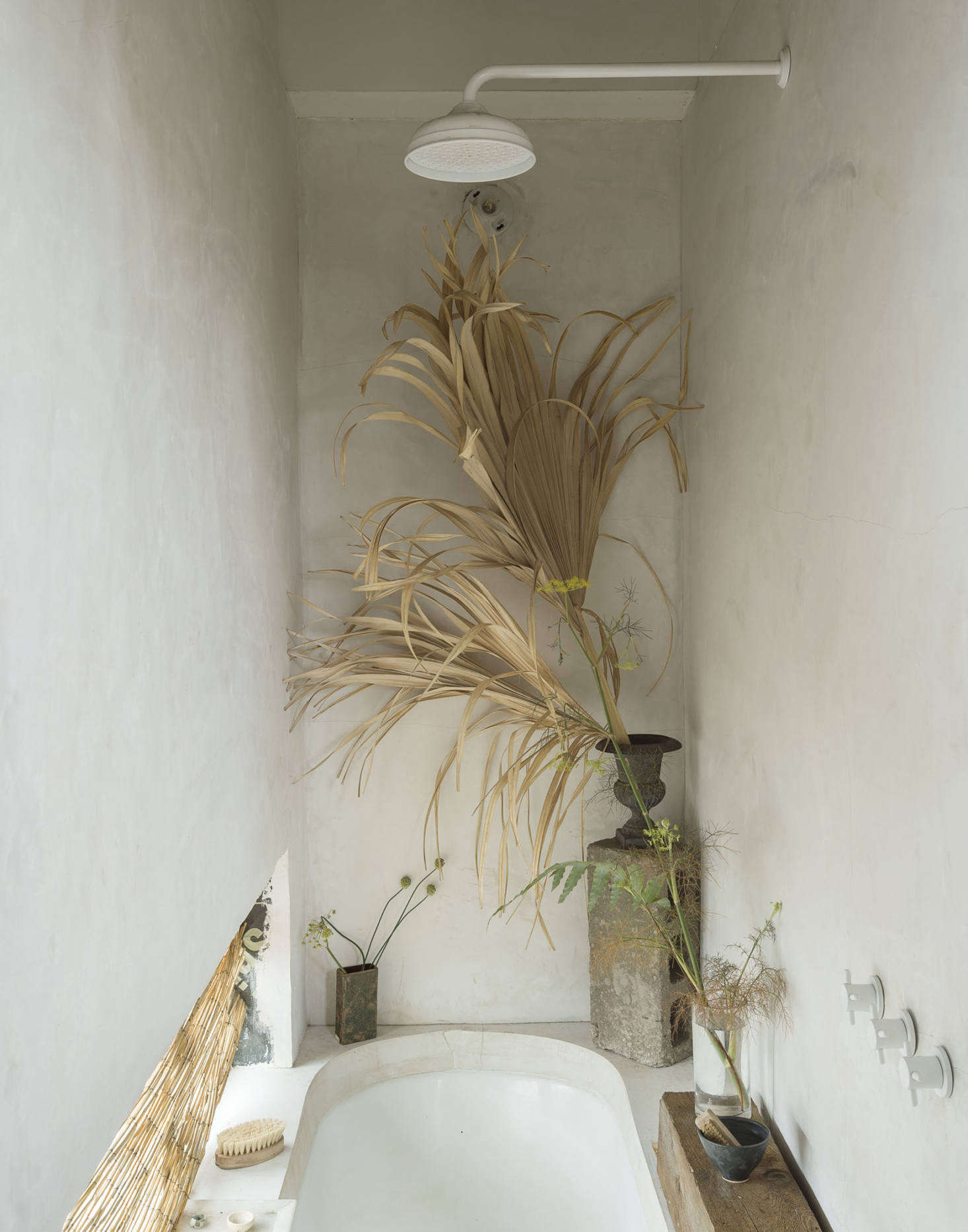 The sunken tub is a vintage cast-iron clawfoot that came from one of Fabr's earliest building projects, and the fixtures and tile were all leftovers from various other projects. The tub is surrounded by a 4-inch concrete topper, and the walls are cement stucco. The shower fixtures are from California Faucets.