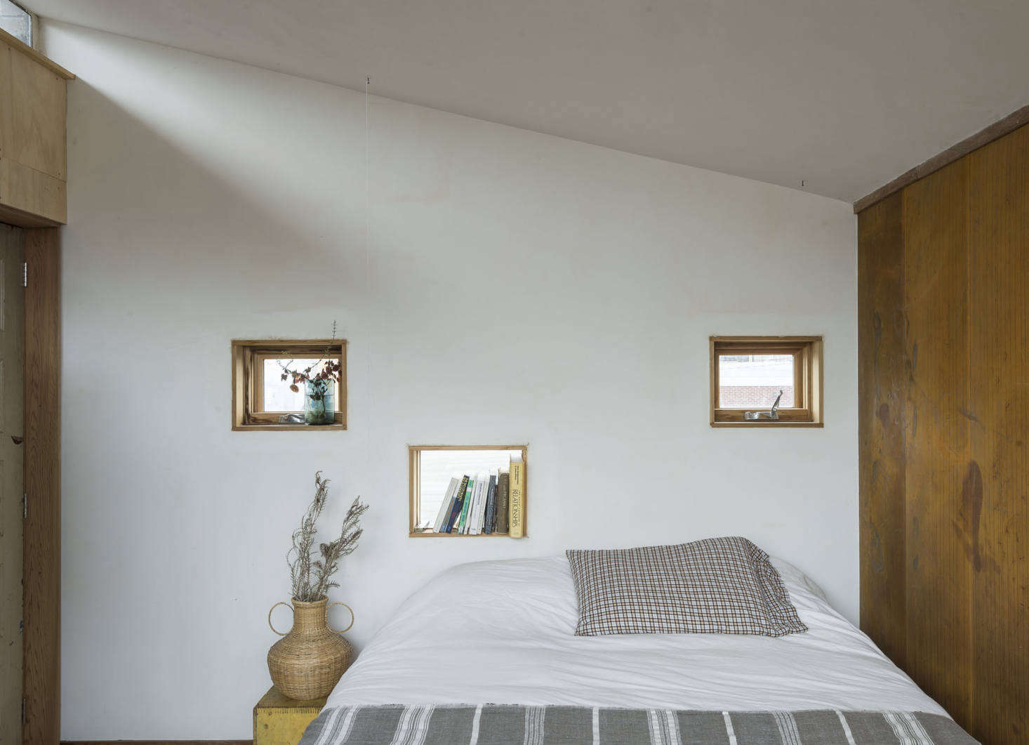 The bedroom wall is made of concrete blocks; the Sierra Pacific windows are slotted into a trio of voids.