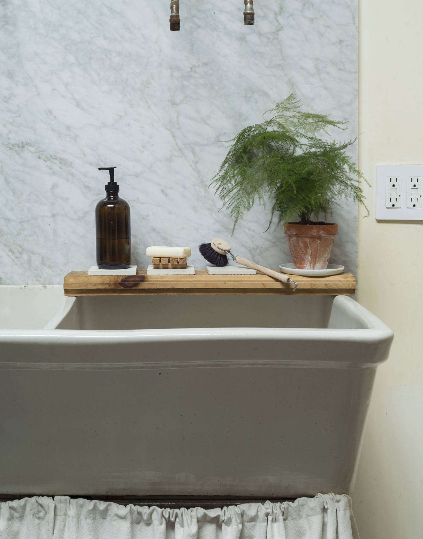 A leftover piece of pine flooring serves as a ledge for sink essentials.
