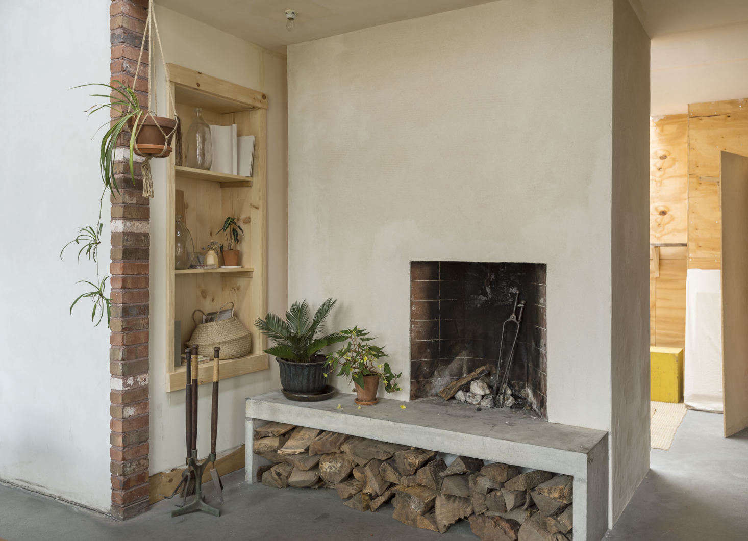 "The double-sided Rumford fireplace is made of concrete masonry block. ""We designed and cast in place the concrete hearth, which also acts as a bench,"" Bretaigne says. ""We have a lot of fires in the winter; it's like 18th century Russia in here."""