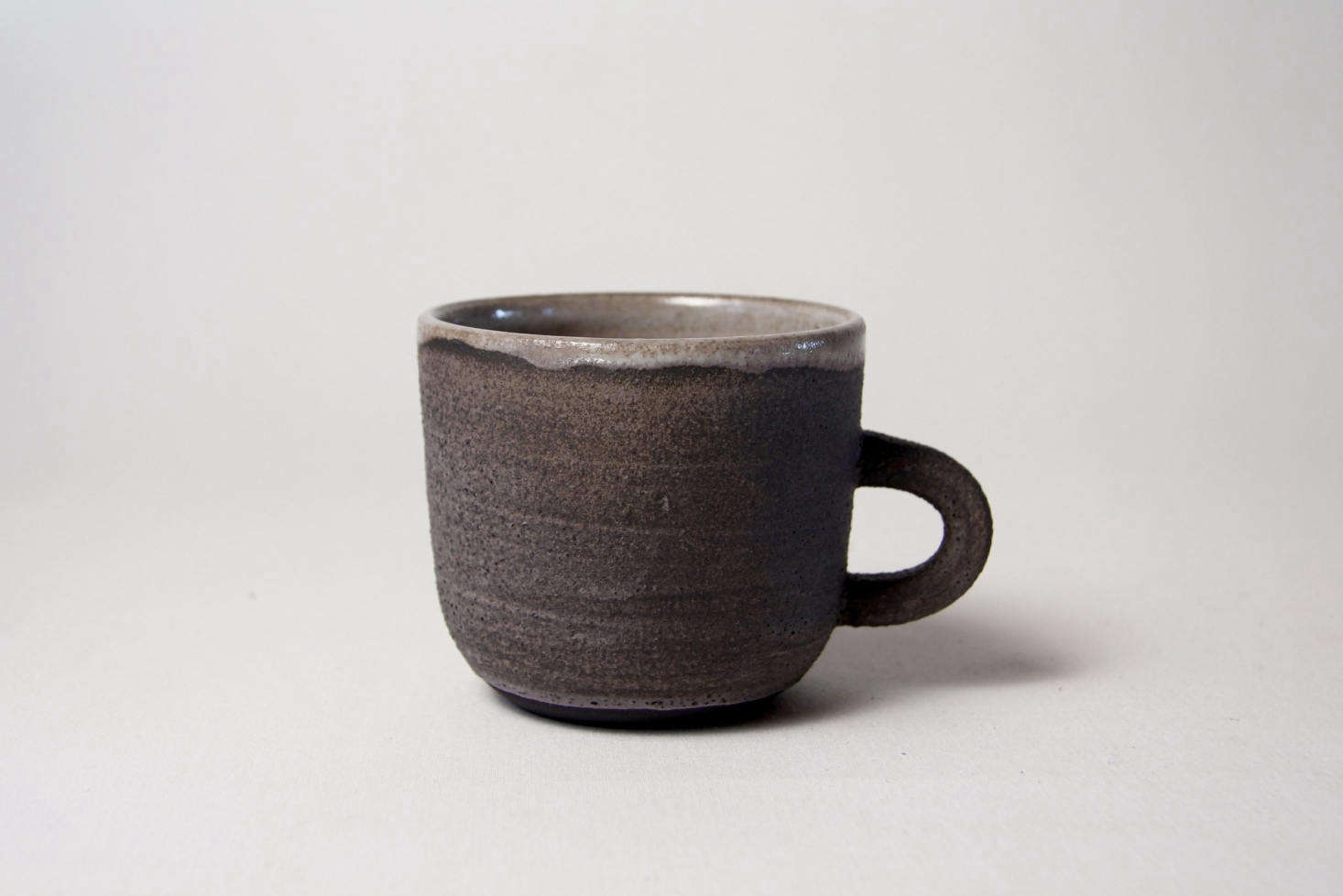 In the coastal community of Lincolnville, Maine, ceramicist Ariela Kuh of ANK Ceramics handcrafts tableware in a charming studio and finishes each piece with glazes mixed in small batches. Shown above is her Black Sand Mug, whose rough texture and purple-black glaze are evocative of its namesake.