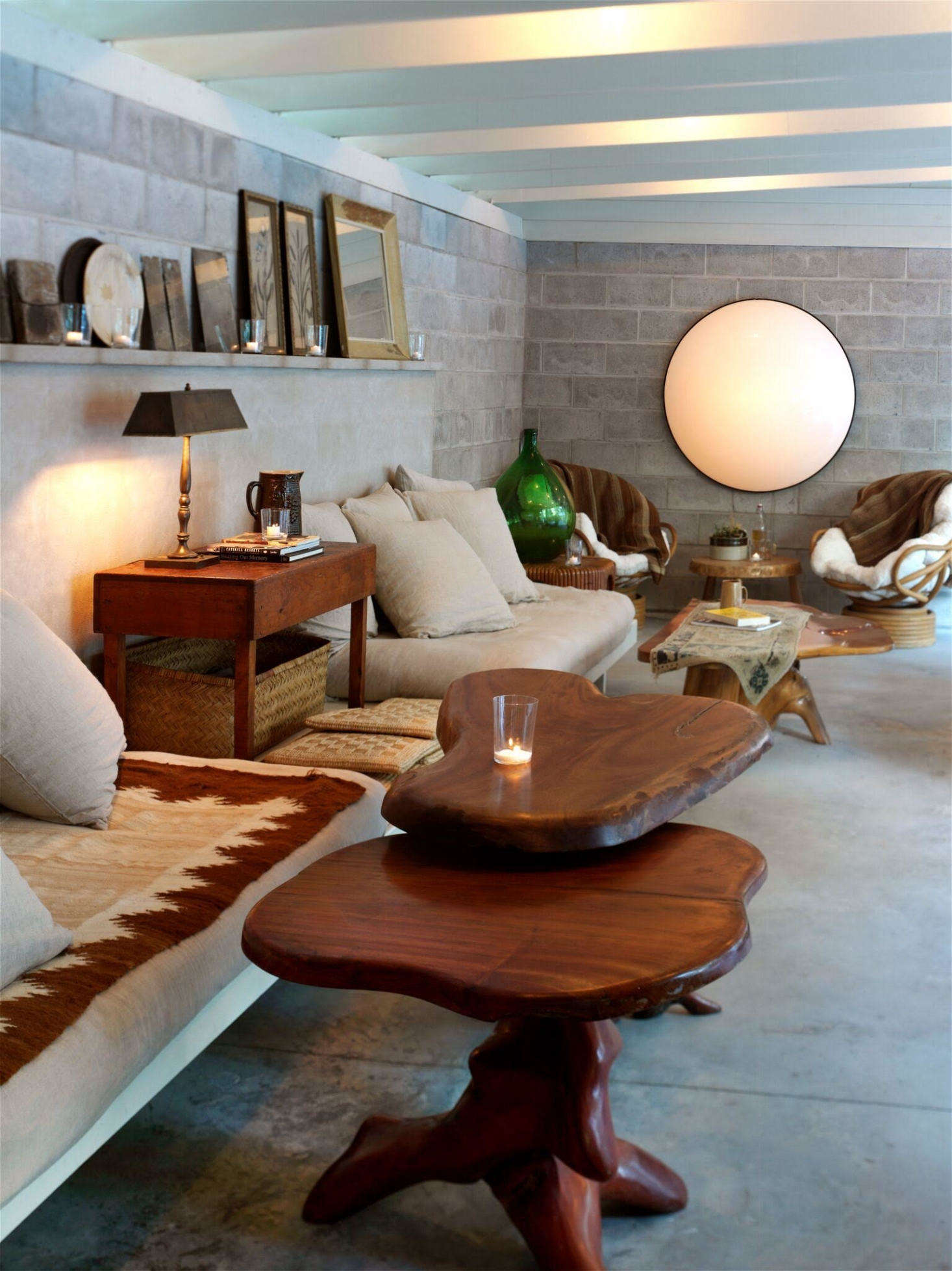 In the adjoining lounge, tree stump tables and masonry walls &#8