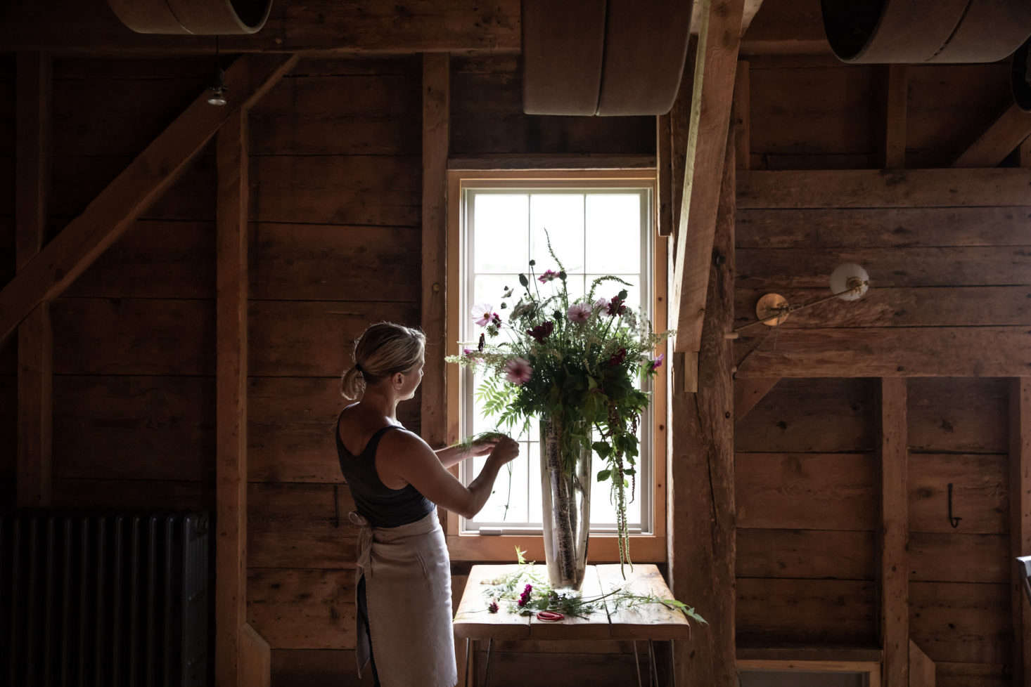 French takes a moment between cooking to arrange the flowers for the evening. At dusk, French herself goes around to each table to light candles.