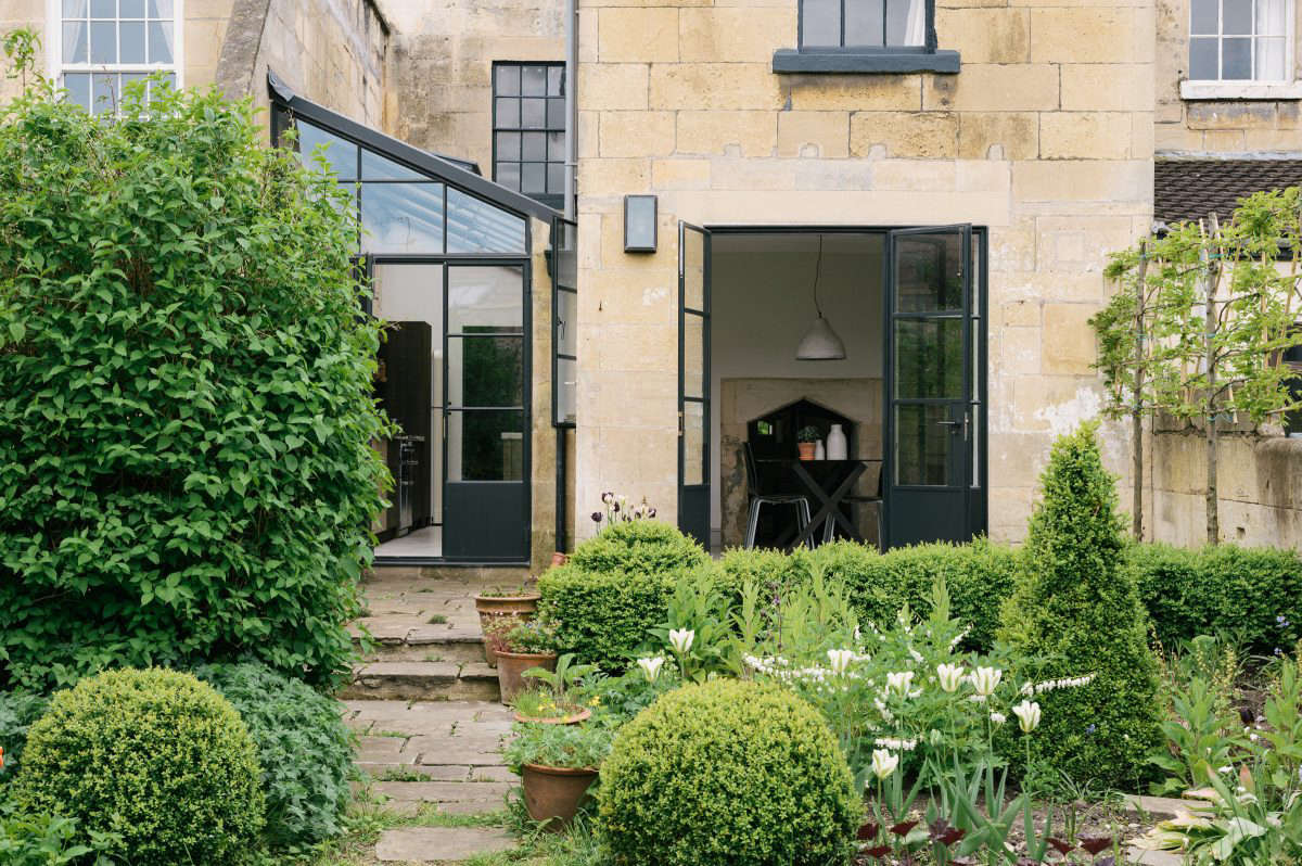 The house is part of a series of connected cottages. Steel-framed French doors open the dining area to the enclosed garden, framed at one end by a Bath stone wall. The couple reused stone to build the back terrace. &#8