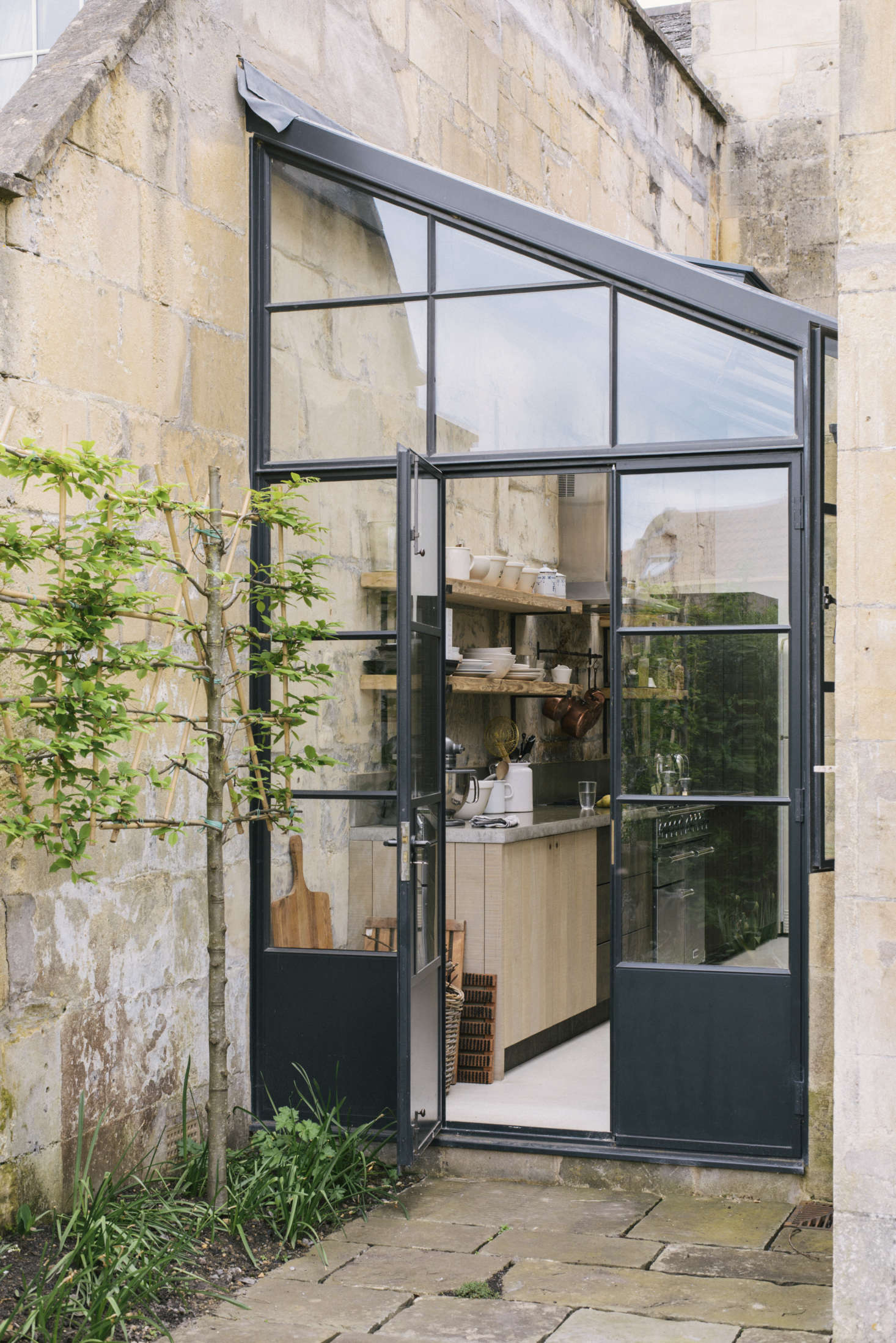 The greenhouse-style extension is fitted between two wings of the house (scroll to the end to see a stepped-back view). The couple worked with Mark Watson of architect-surveyors Watson, Bertram & Fell to draw up plans and secure building permissions; the bespoke steel-framed doors are by Fabco.