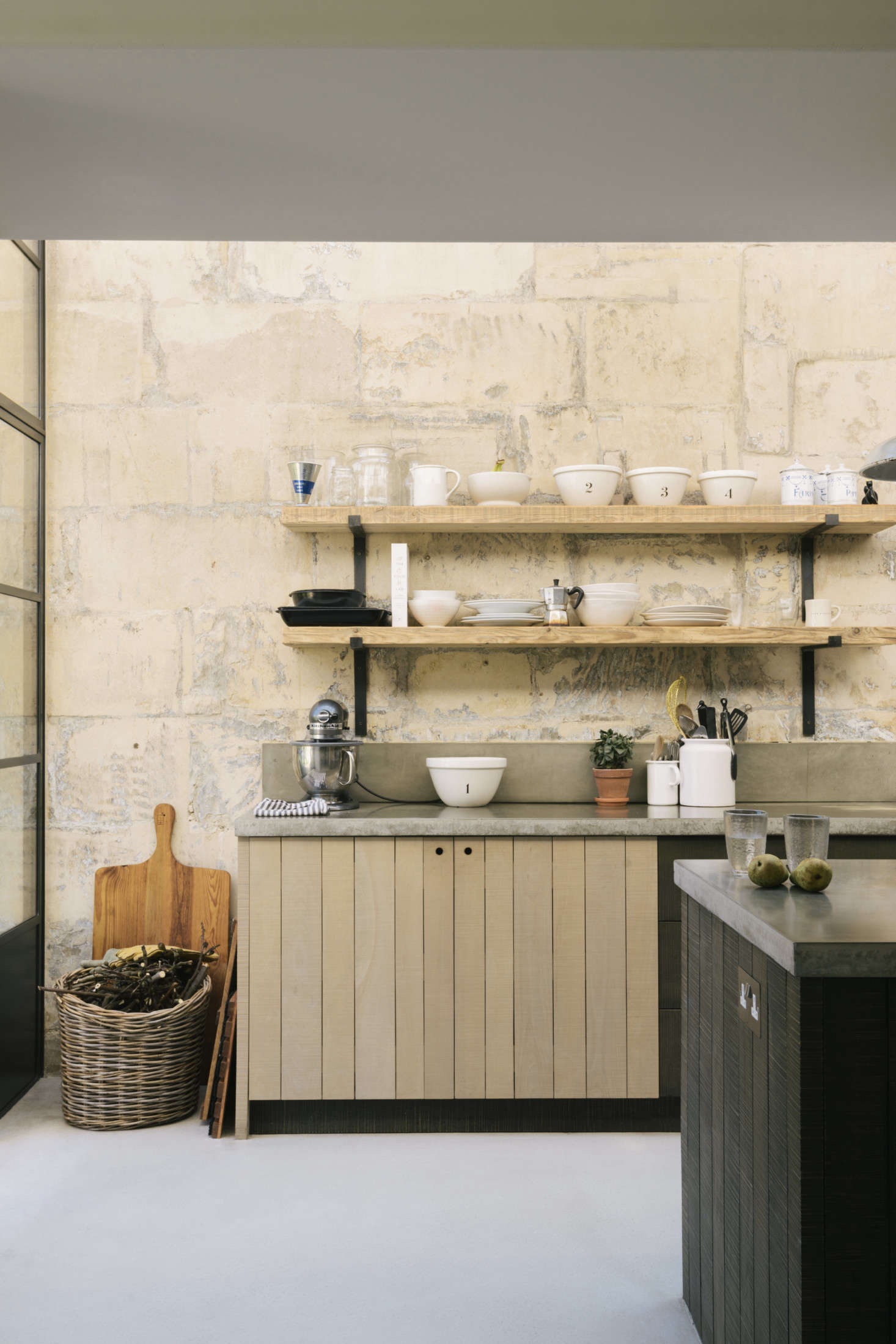 A lineup of black-and-white dishware, including numbered nesting bowls,line the open shelves. (See Burleigh Pudding Basins for the design with blue numbers.) Admiring the basket? Go toObject Lessons: The Almighty Wicker Basket.