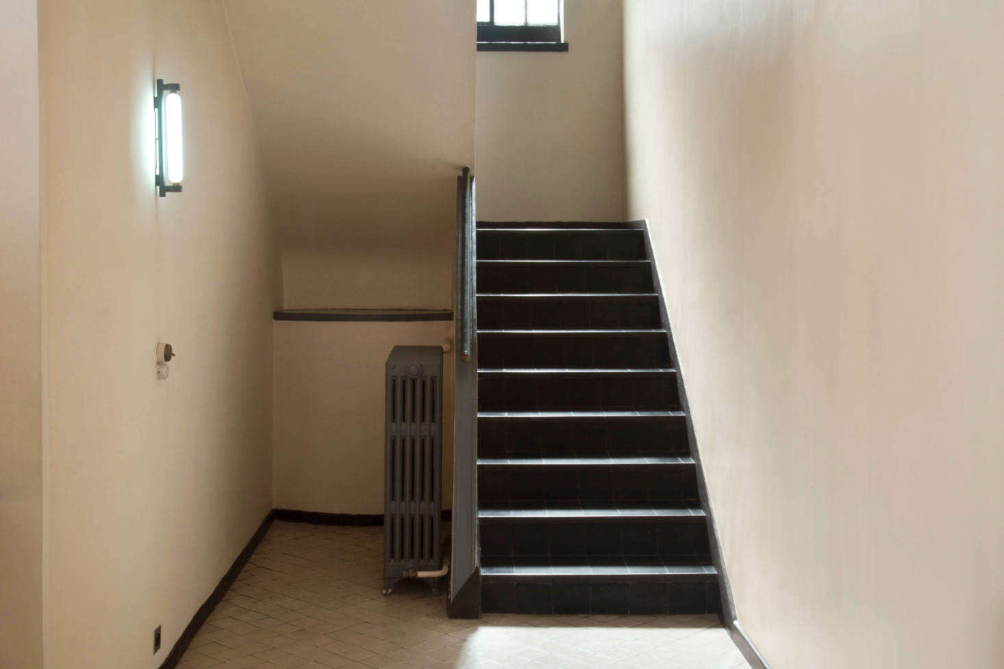 The foyer walls are painted Ivory and the staircase and radiator are Dark Gray. &#8