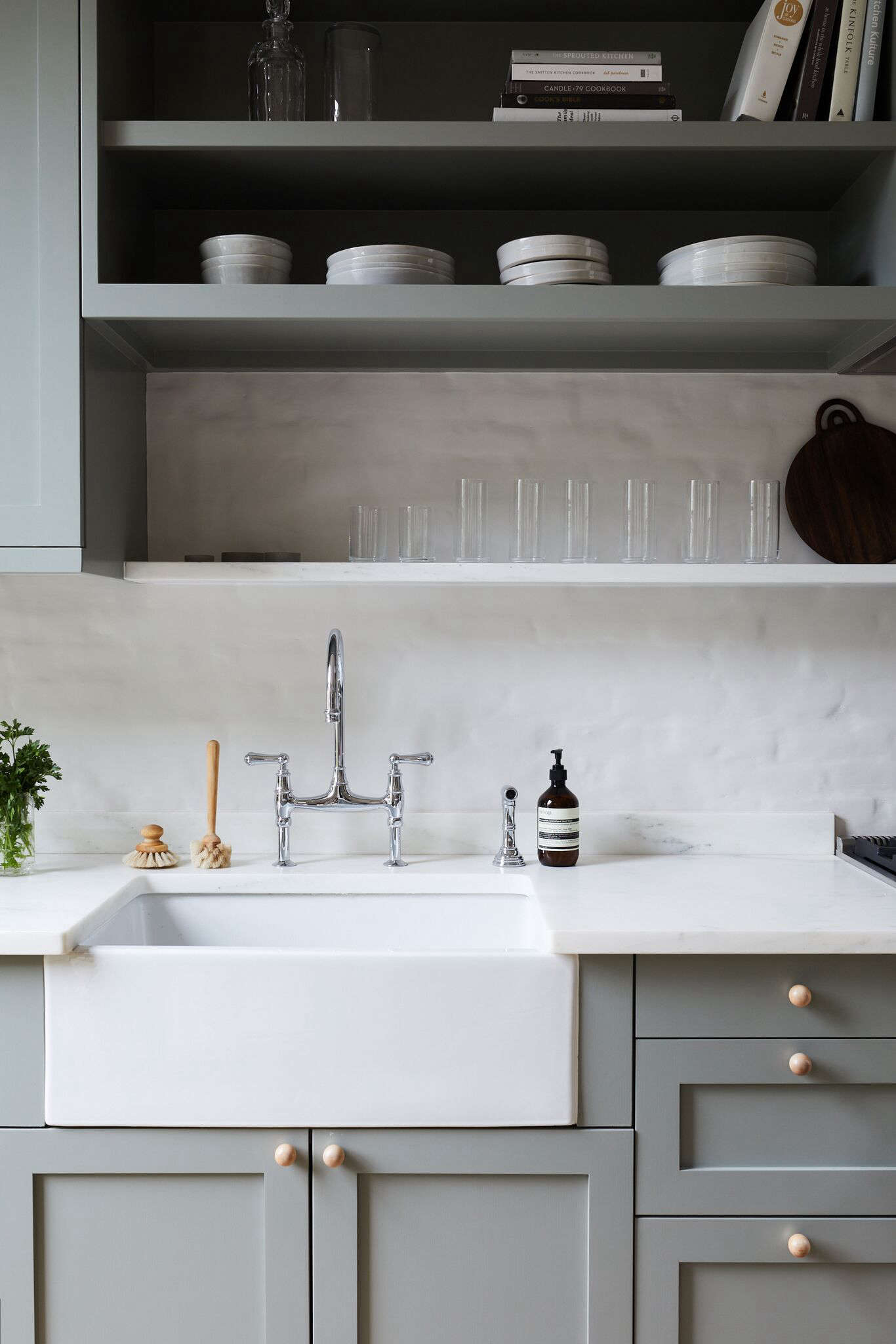 The owners and their team chose a farmhouse sink and chrome bridge faucet for a classic look they would never tire of. Photograph by Nicole Franzen from Rehab Diary: Monochromatic Luxe in Park Slope.