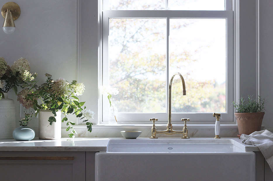 A large apron-front farmhouse sink anchors the L-shaped kitchen. It&#8
