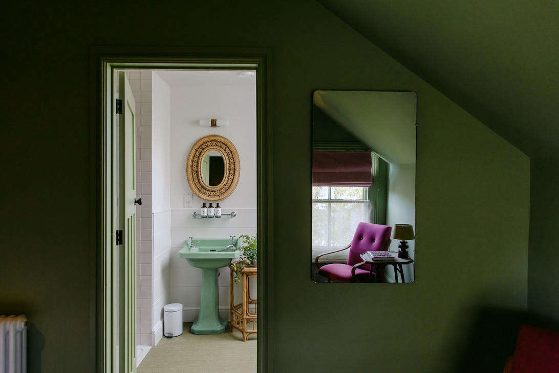 A nice tonal dose of mint and olive green from the guest room walls to the bath fixtures.