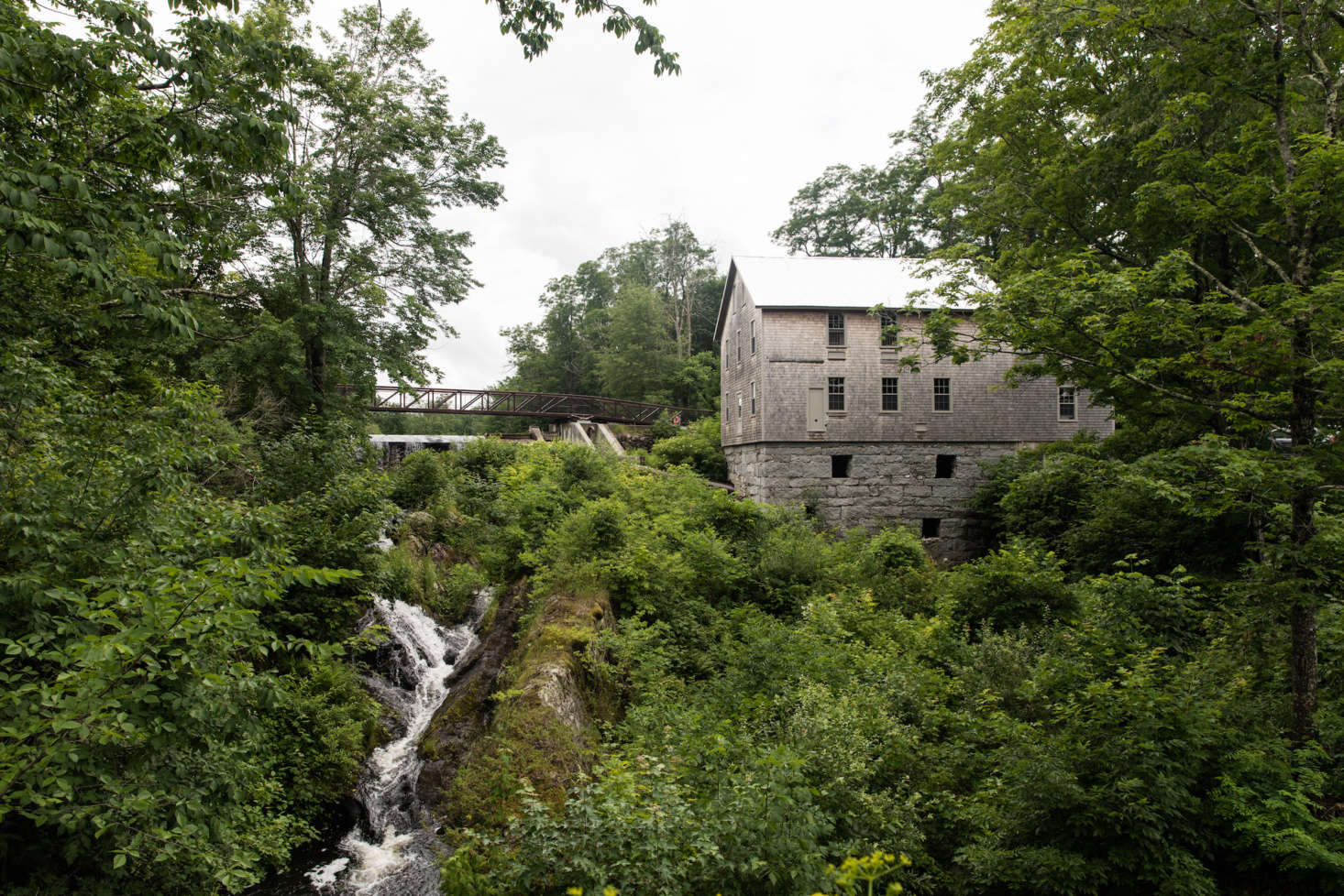 The Mill at Freedom Falls, where the Lost Kitchen is located, is perched above a wide creek. The 34 building was formerly a gristmill, then a turning mill, but had been abandoned for decades and was in danger of falling into the creek before local conservationists and Cold Mountain Builders worked to restore it, shoring up the granite foundation and replacing the timbers.
