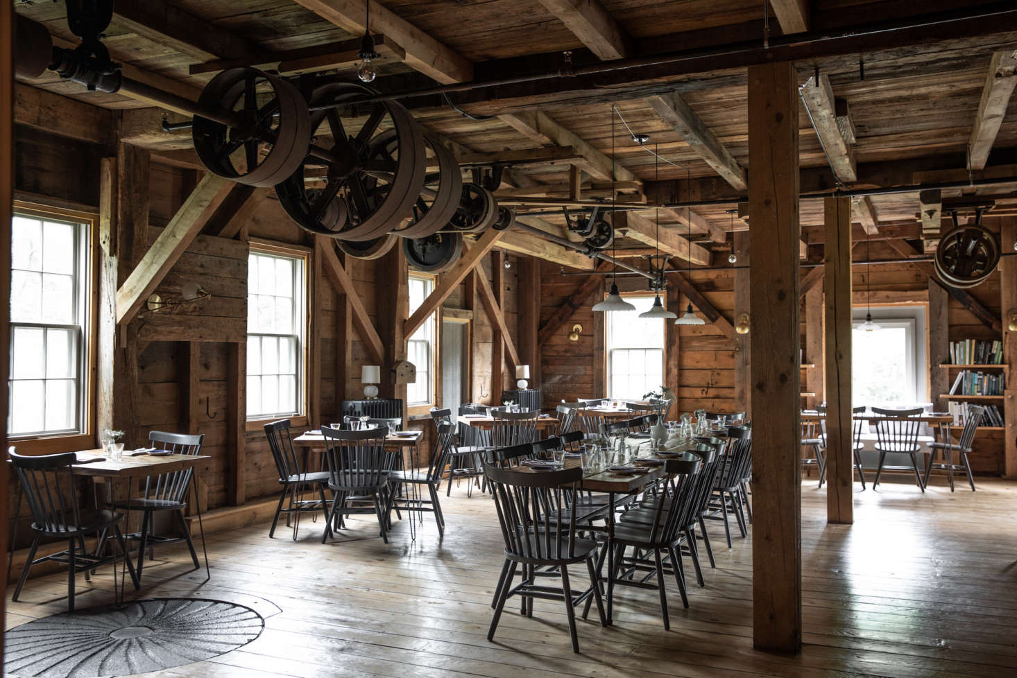 Inside, remnants of the old mill remain: pulley systems and an old millstone, inlaid in the floor. French fitted the dining room simply, and all herself, with hand-built tables and painted spindle-back chairs. She also had a vent and air duct installed to facilitate the working kitchen.