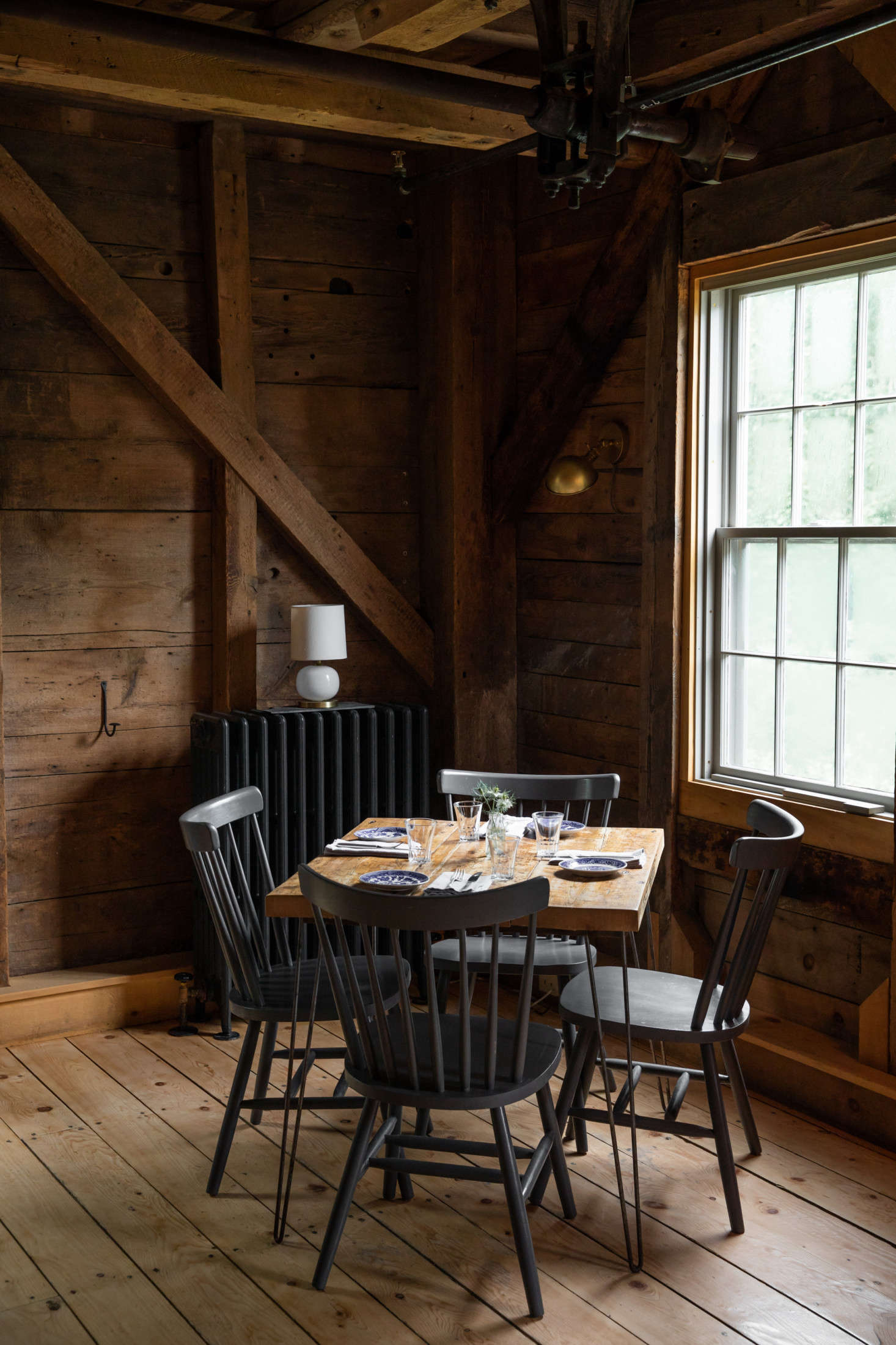 French built the tables with help from a local carpenter, using salvaged wood and metal hairpin legs. The chairs are from Hayes Unfinished Furniture in Brewer, Maine, painted in Benjamin Moore&#8