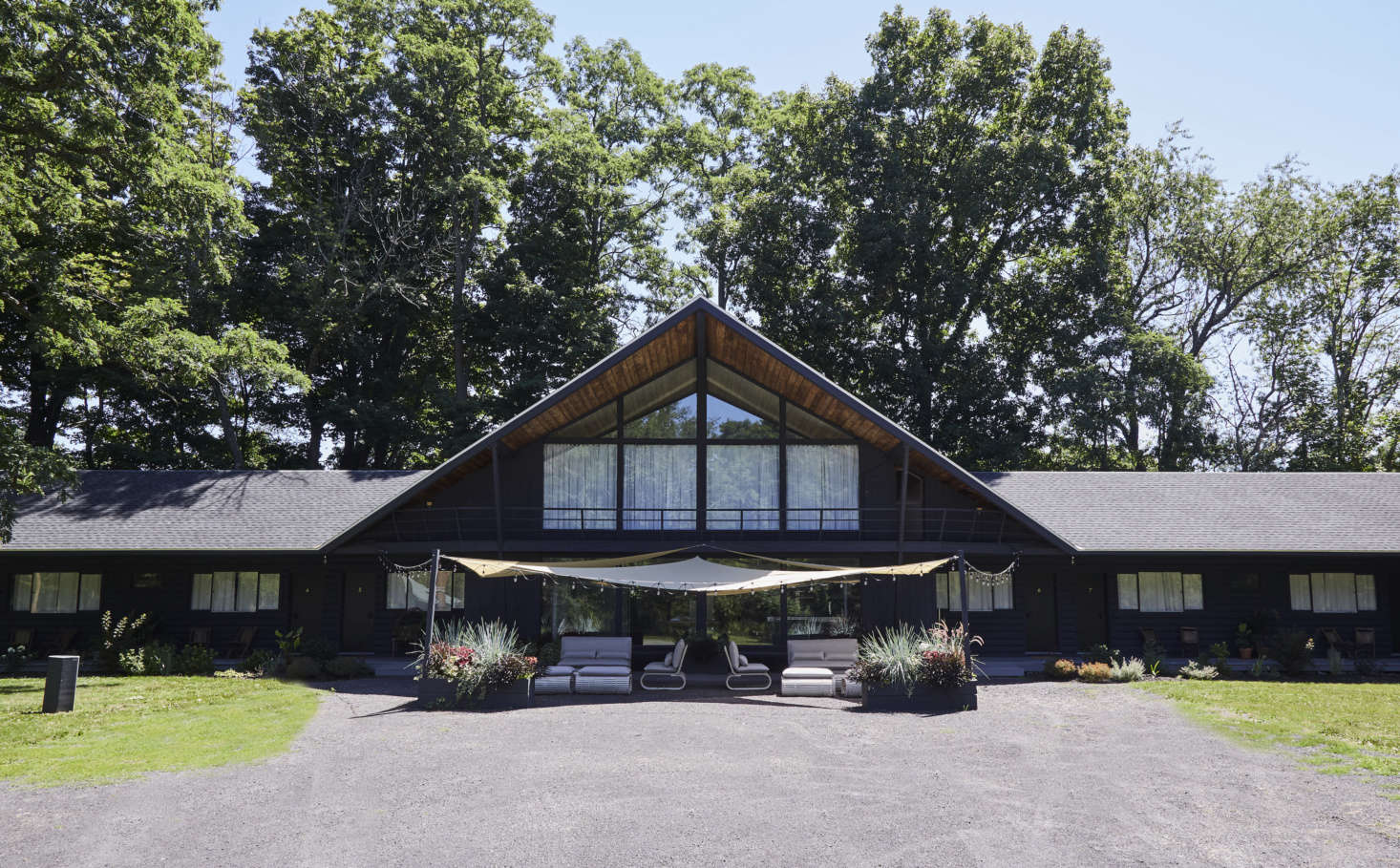 """The lodge is in the town of Greenville, New York, 30 minutes west of Hudson and will be open year-round (there's nearby skiing). It has a new front patio with a canopy that shades wicker furniture from Stori Modern's Novel collection, plus a new asphalt roof. """"The roof made a huge difference in the overall look of the building,"""" says Pflug. """"It's not something I 'see' anymore, but the overall effectmade the buildinglook new."""" (Scroll to the end to see the structure as it was.)"""