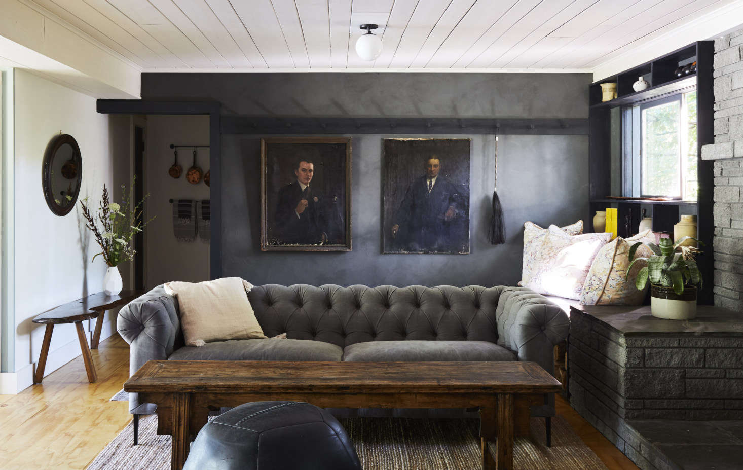 Rather than taking a modernist tact, Pflug furnished the lounge with classic pieces, such as this Chesterfield sofa from Perigold, and enlisted a specialist to apply clay plaster to the walls in a moody gray (they used American Clay; read about the finish in Remodeling 101: Modern Plaster Walls).