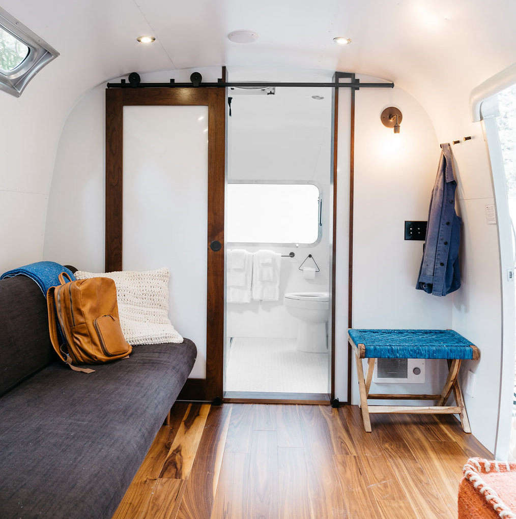 The interior of an Airstream, with a view into the bathroom (stocked with Malin & Goetz toiletries).