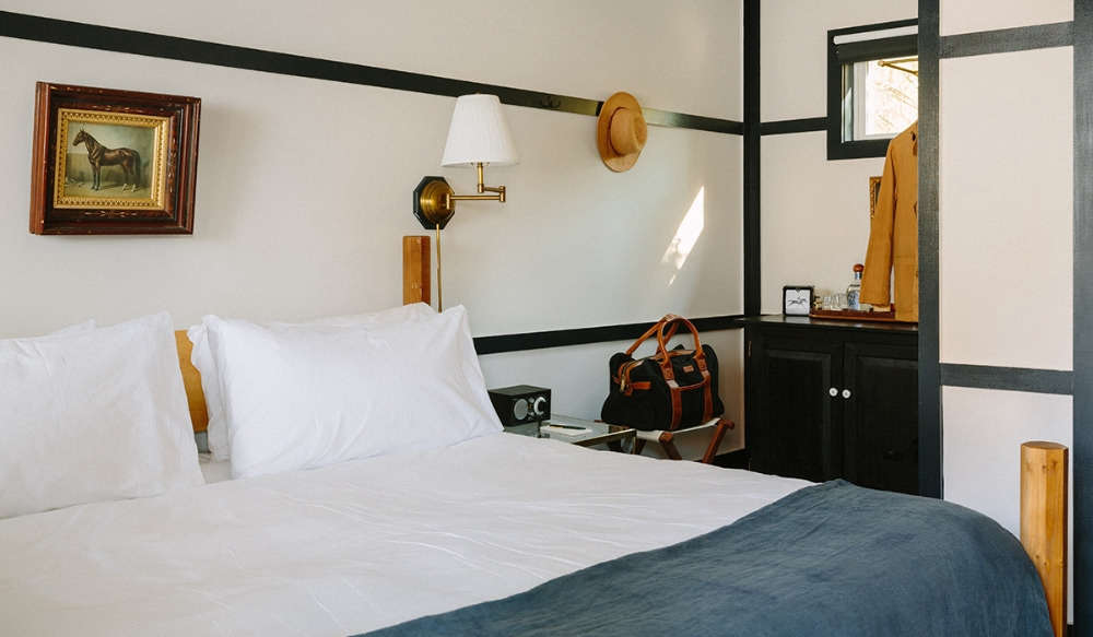 Each of the 12 guest rooms is painted white with dark-painted trim boards, echoing the hotel's exterior. Bonus: The trim peg rail doubles as a place to hang your hat.