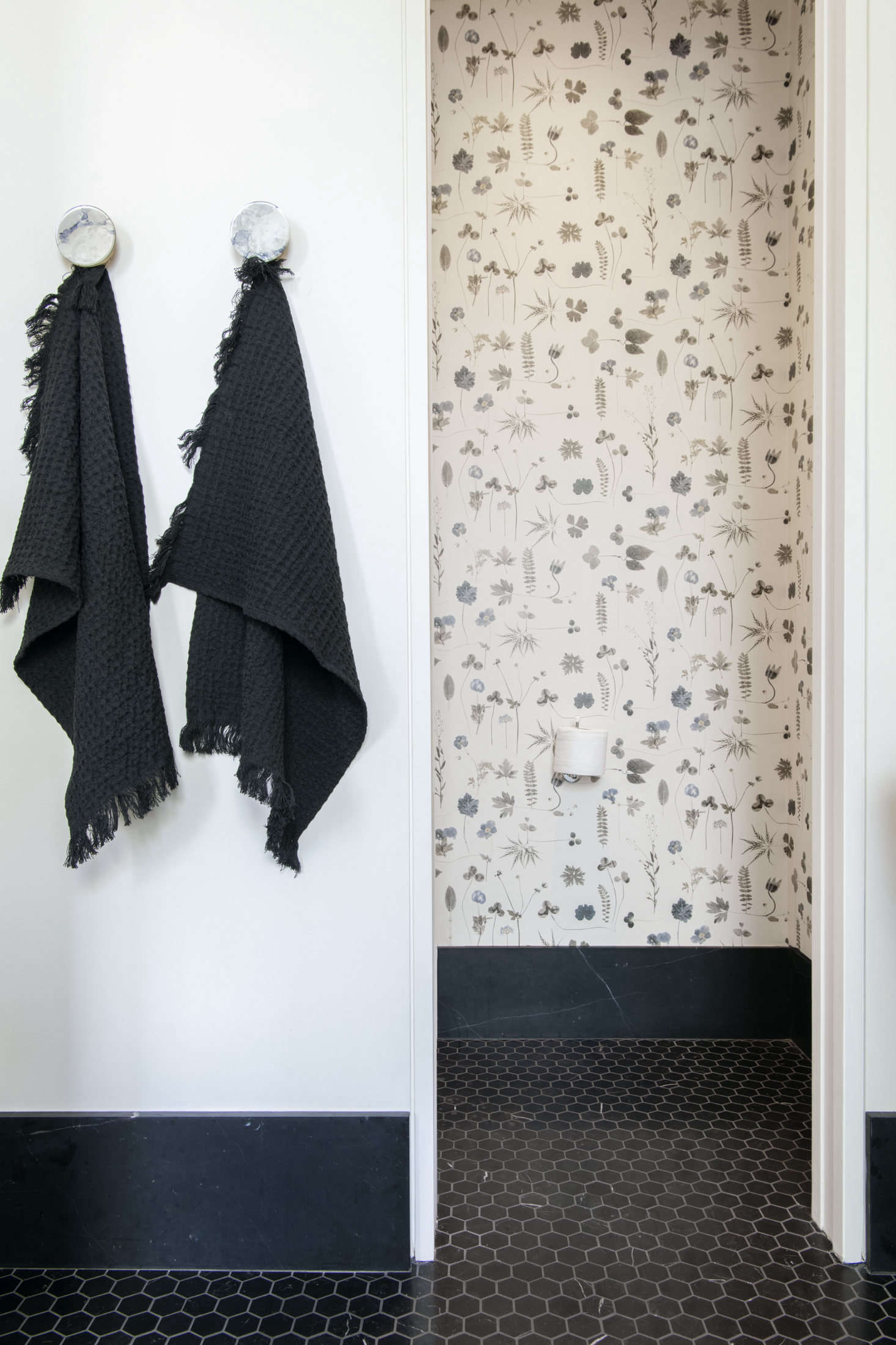 Soft waffle towels and botanical wallpaper add a soft, natural touch.