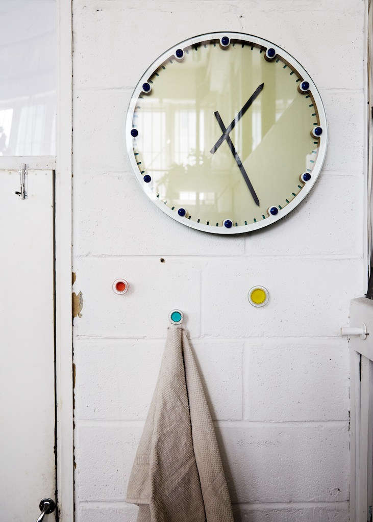 Bespoke hooks are screwed into the whitewashed, breeze-block walls beneath a prototype clock by Fabien Cappello.