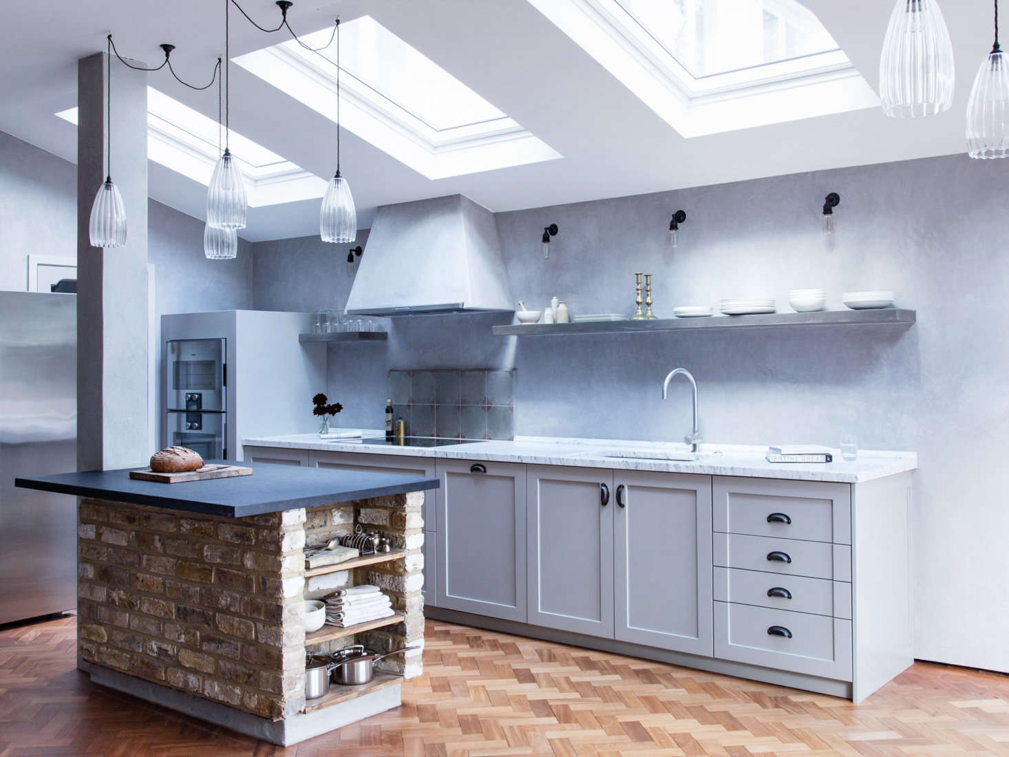 A clever use of interior brick: A kitchen island that references an indoor fireplace or pizza oven.