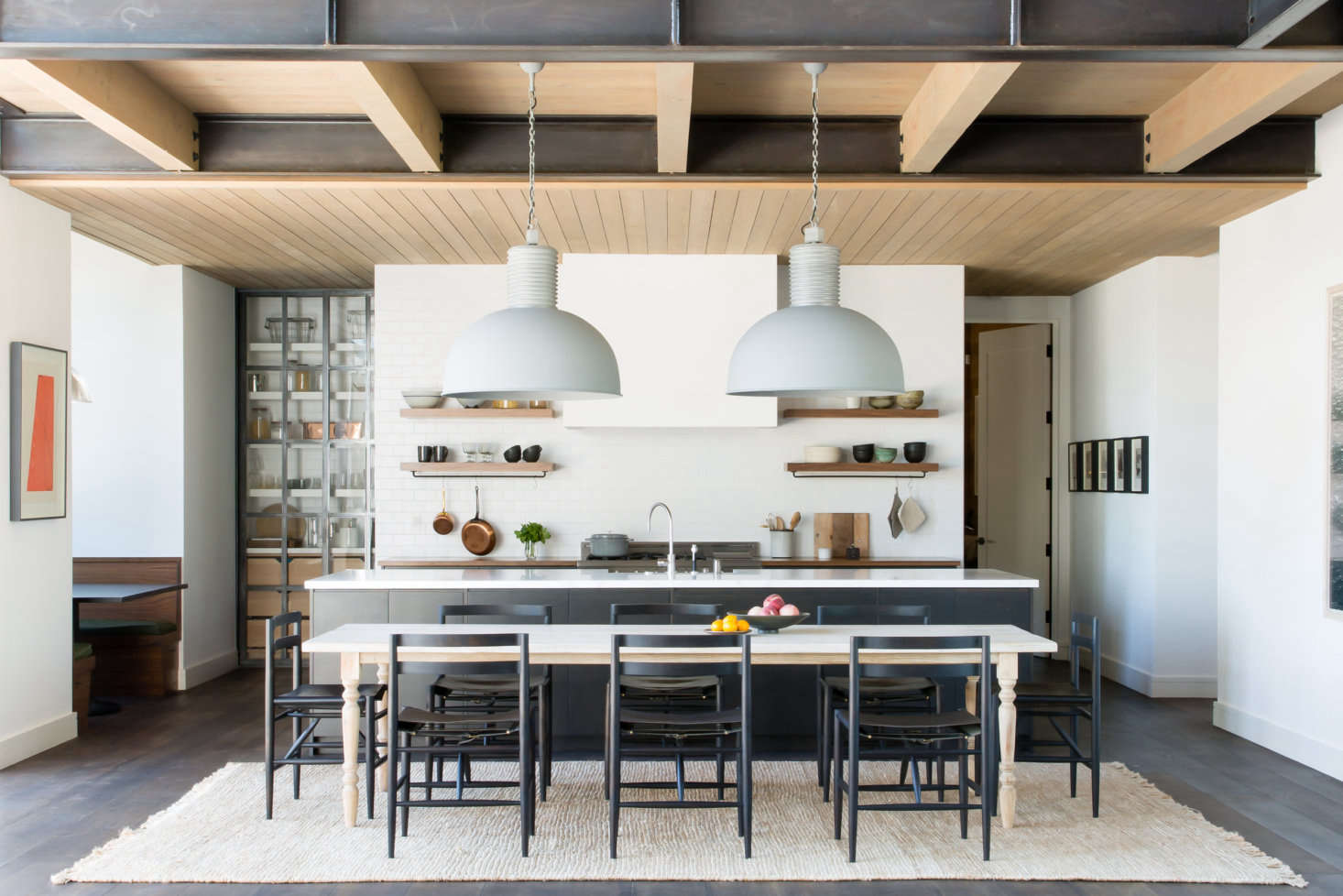 In a Tahoe kitchen by ABD Studio, a pair of oversized industrial lights hangs over the dining table.