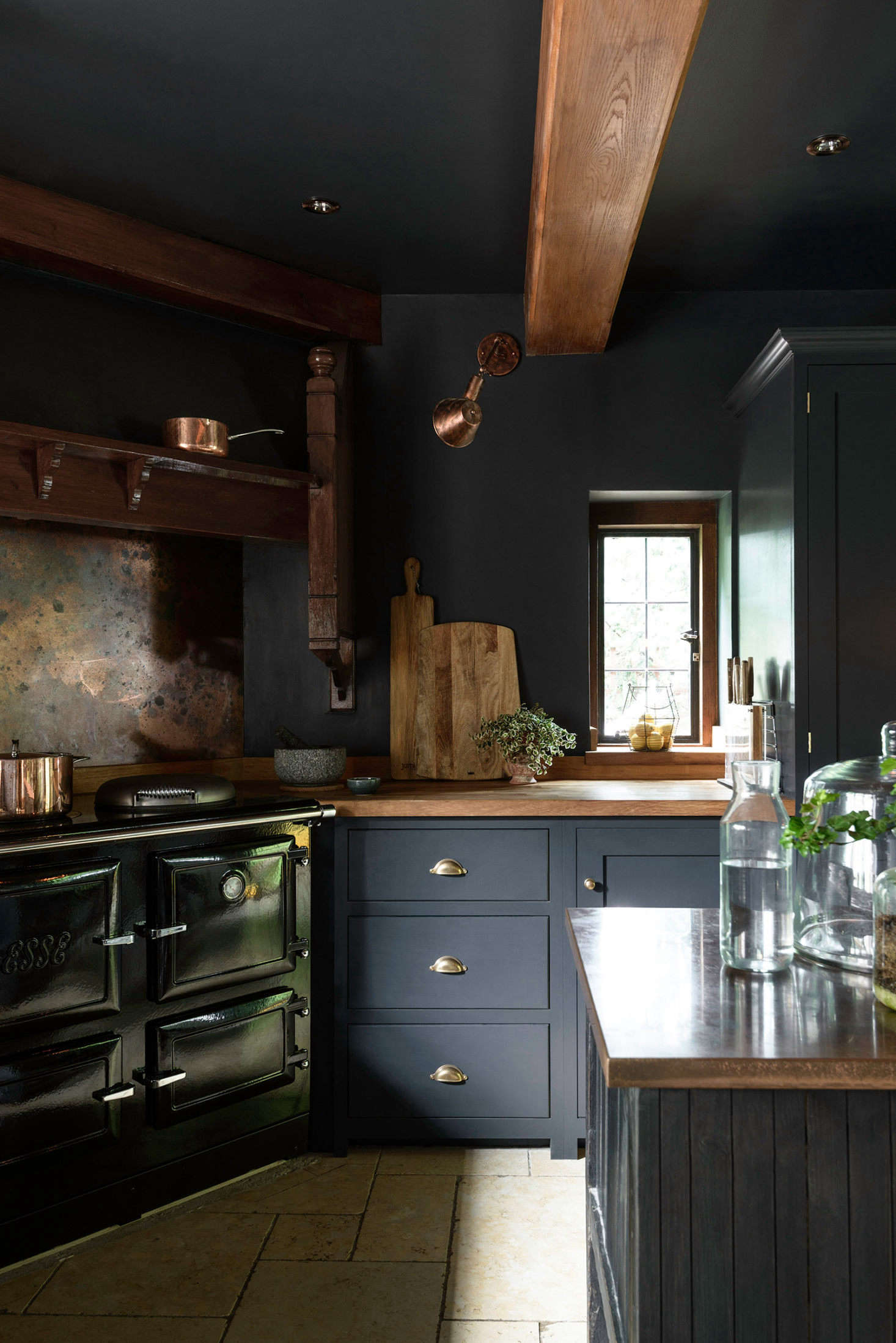 Most of the kitchen is newly built, but the wood fireplace mantel over the cast iron Esse stove is original to the home. The patinated copper backsplash and copper worktop on the island are warm, glowing counterpoints to the matte dark paint on the cabinets.