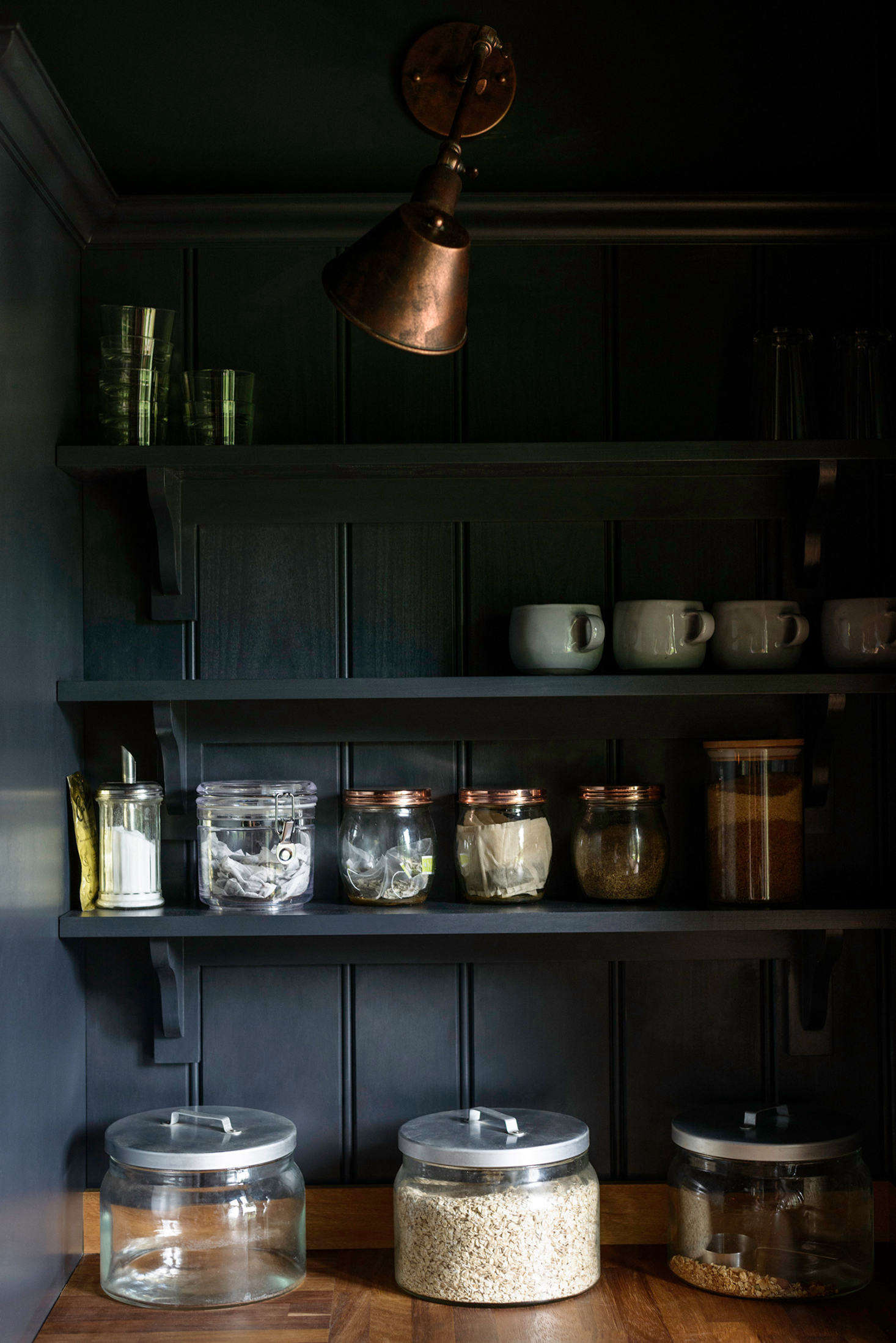 Simple jars filled with breakfast essentials occupy a small open-shelving corner pantry. A single industrial copper sconce hangs above.