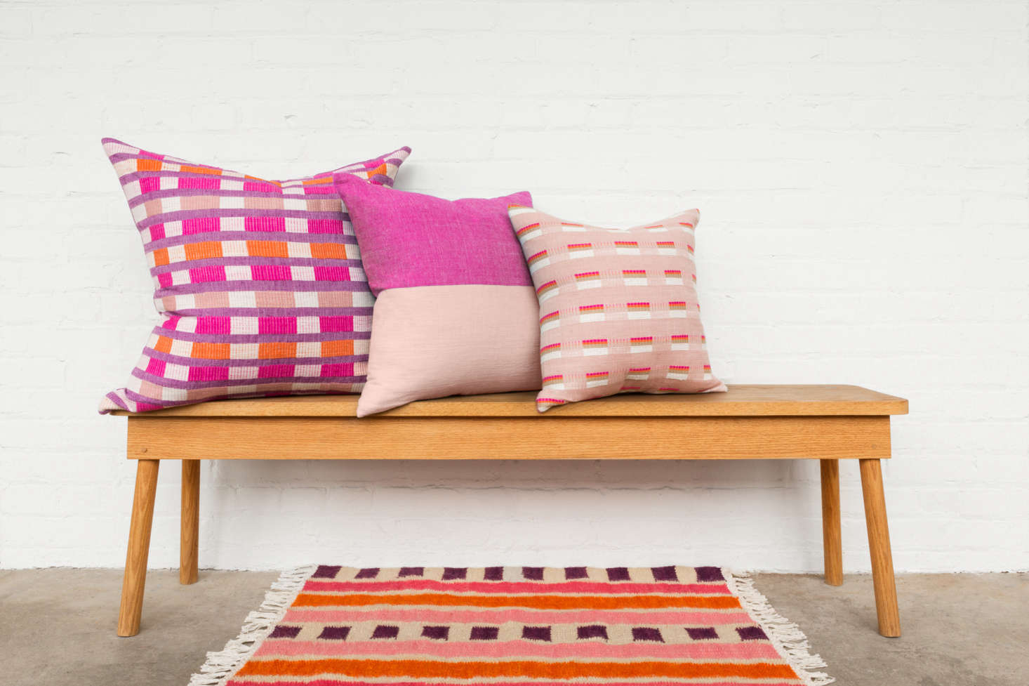 The cerise colorway, shown here in three sizes. The Omo Valley Collection pillows are priced between $5 and $0. The cerise Bana Rug is currently sold out, but it is still available in sable and azure for $5.