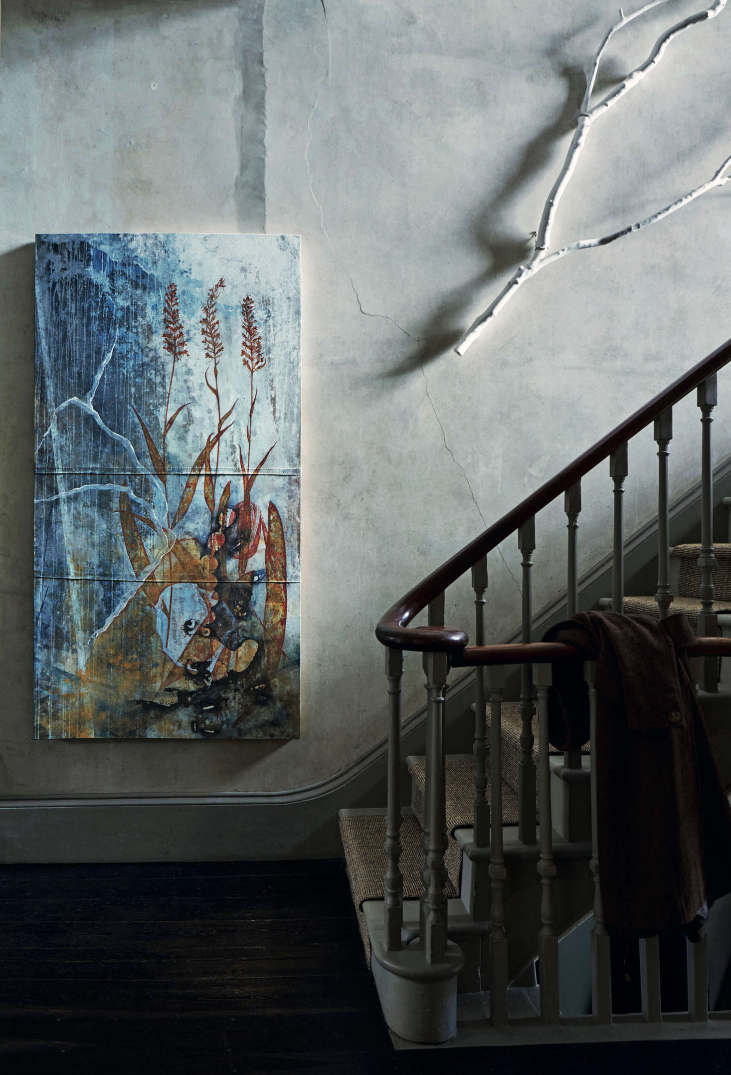 "One of David's paintings and a whitewashed branch hang against bare plaster walls in the entry stairwell. David and Anita live several months a year on the Mani Peninsula of Southern Greece, and David says his work is inspired by the area's natural landscape and its church wall paintings ""richly patinated in their various states of decay."""