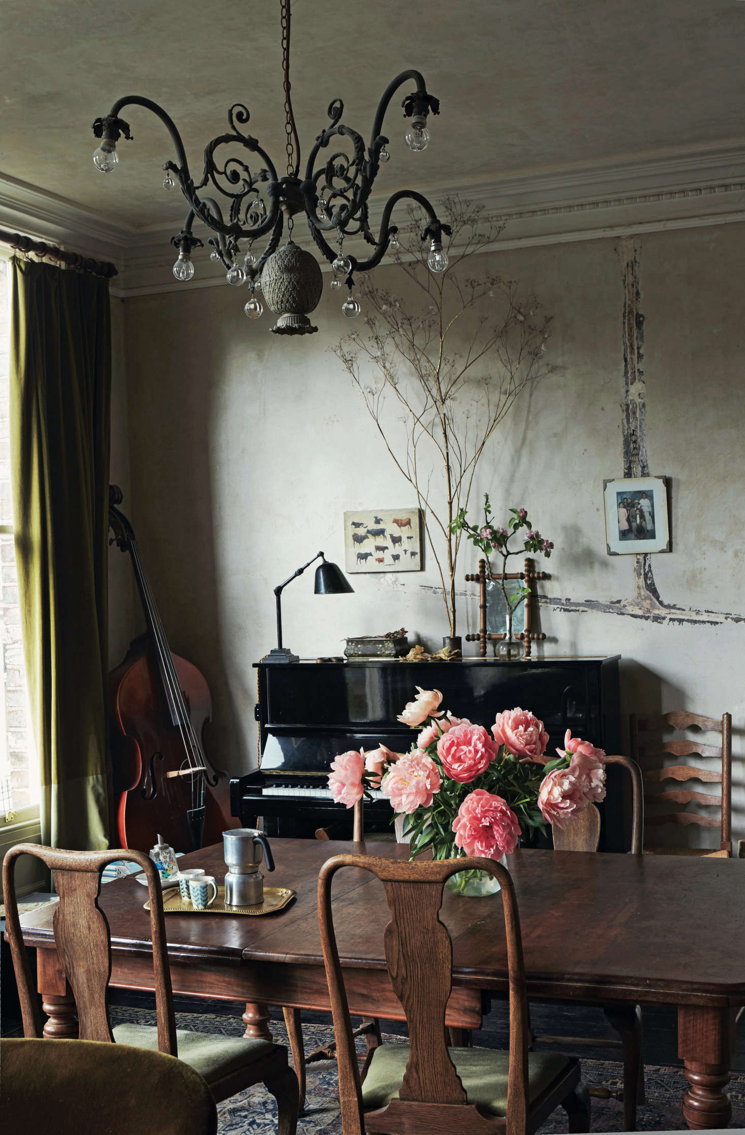 "In Perfect English Townhouse, Ros Byam Shaw notes that the lines of filler on the stripped wall above the piano ""mark out where the pipes for the gas lighting once ran."" She goes on to explain: ""The chandelier is one of David's creations, and incorporates a metal pineapple found at a car boot/yard sale. The painting of cows on the far wall is a study by David's great-grandfather, the celebrated Swiss artist Eugène Burnand."""